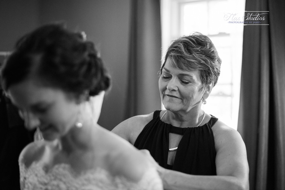 mom helping the bride put on her wedding dress