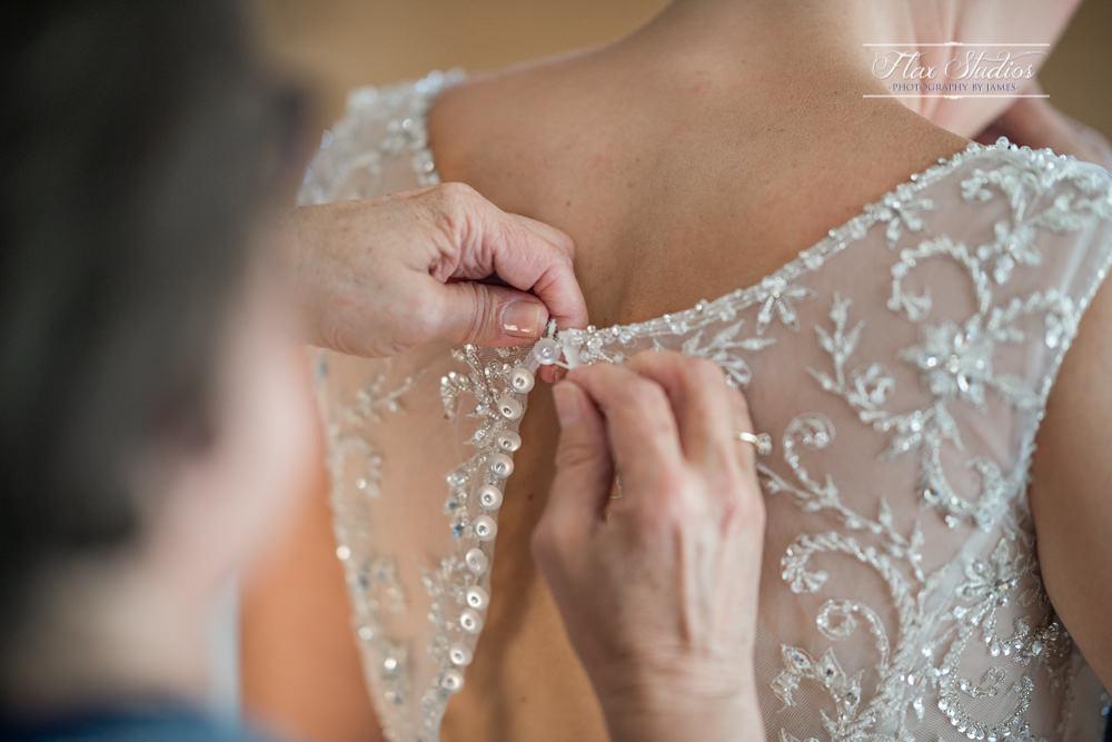 mom helping the bride put on her wedding dress