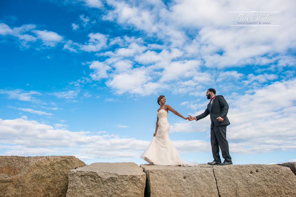 bride and groom walking on the rockland breakwater lighthouse