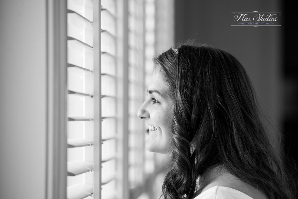 bride looking out the window at her groom at the first look