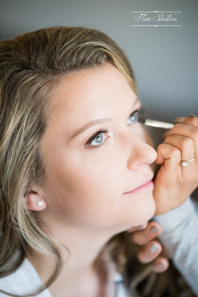 The bride putting on her wedding day makeup