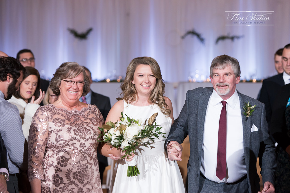 Both of the brides parents walking her down the aisle