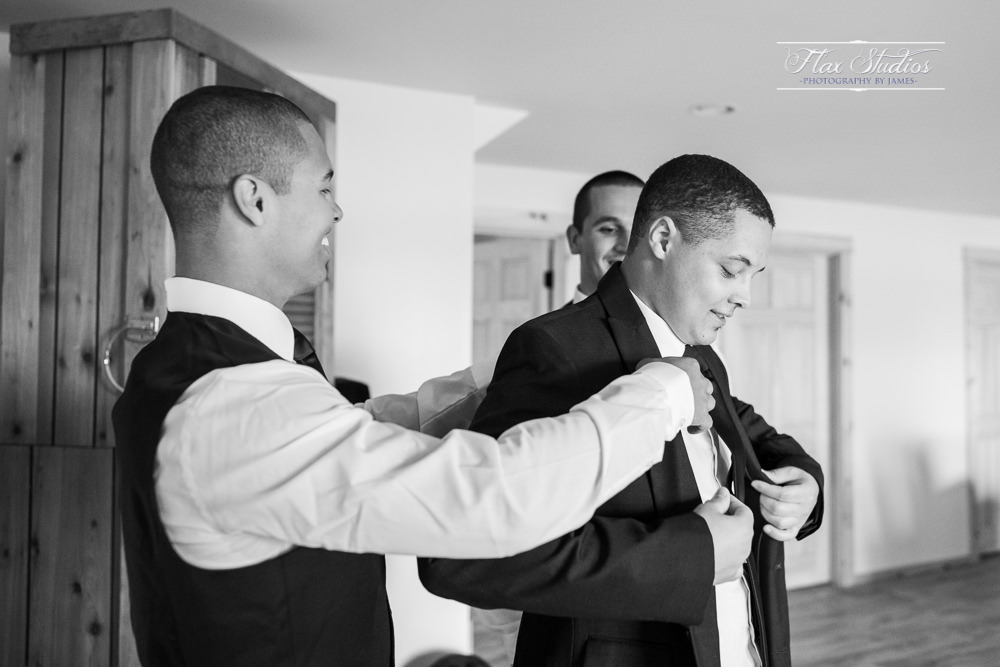 guys helping groom into his wedding jacket