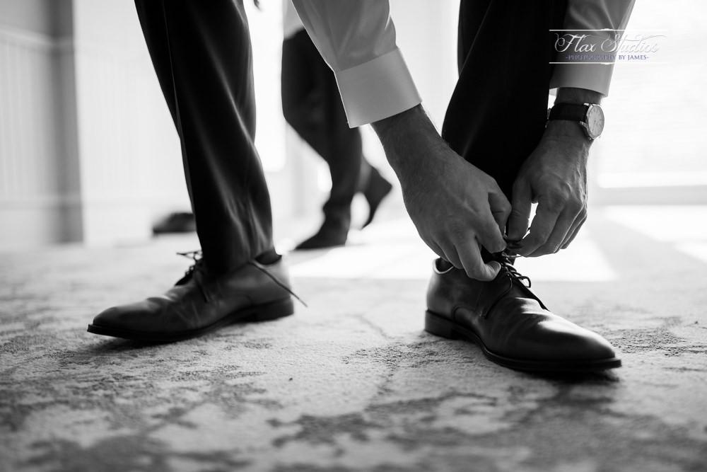 groom putting on his wedding attire