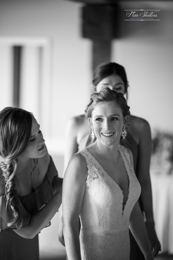 the bridemaids helping the bride into her dress