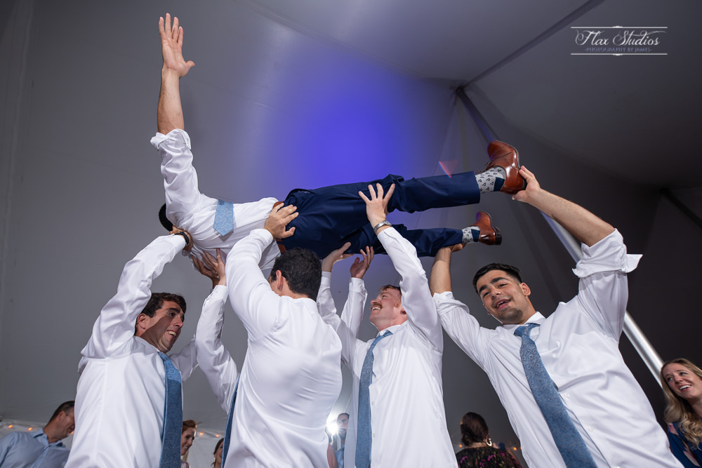 lifting up the groom on the dance floor