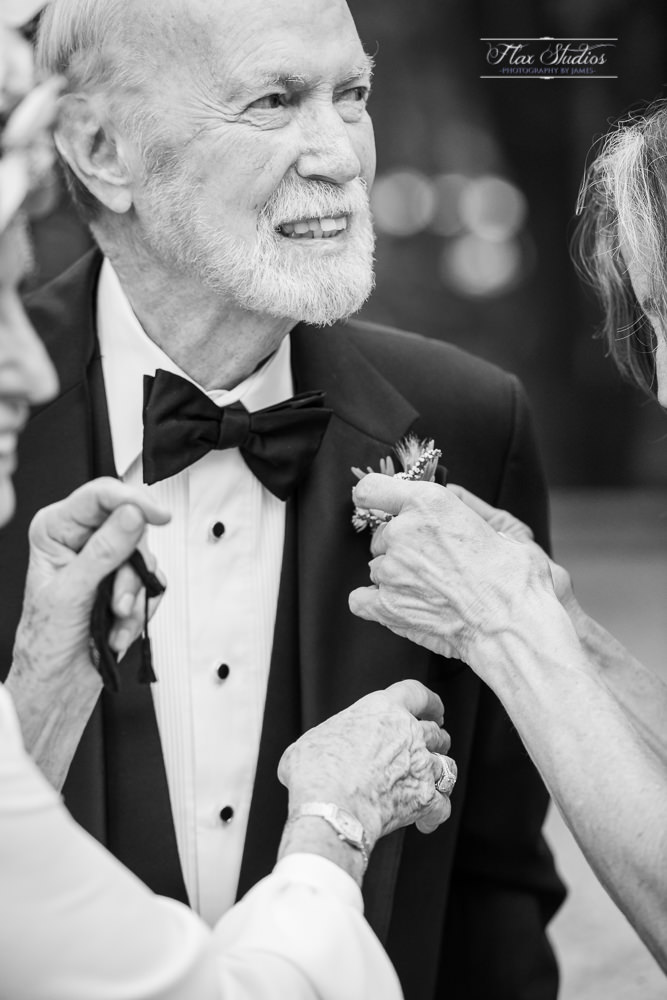 the groom having his boutonniere put on his tuxedo
