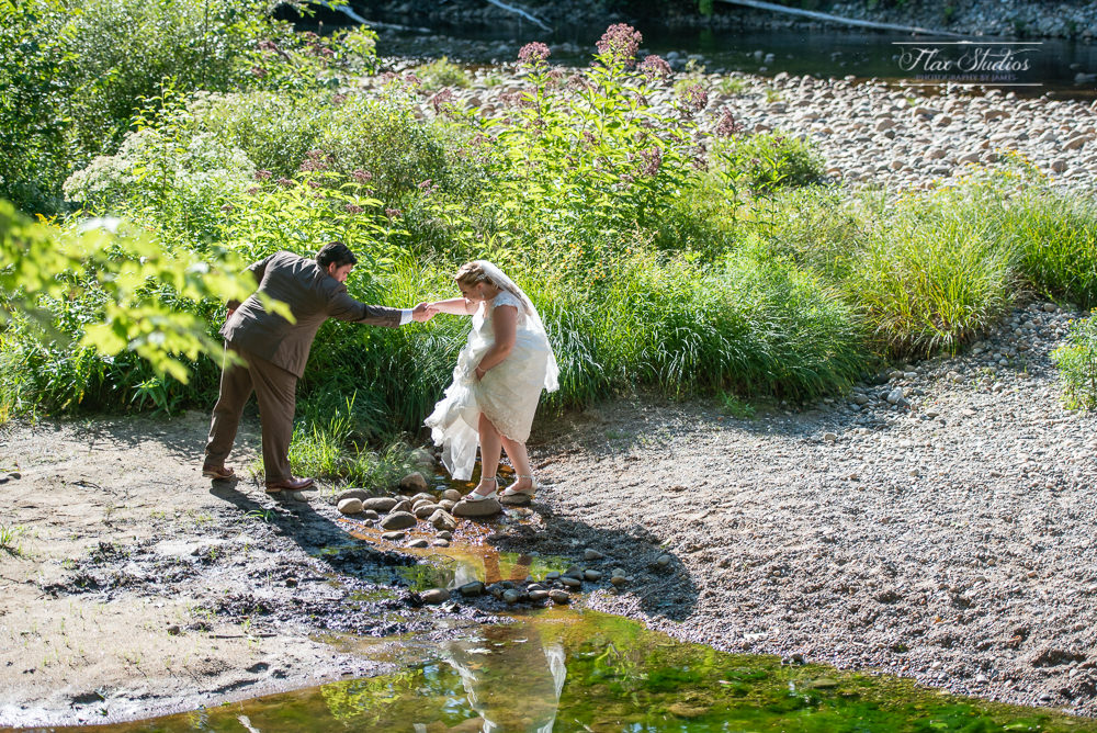 groom helping his bride cross the water