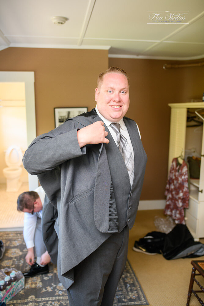 The groom putting on his suit coat