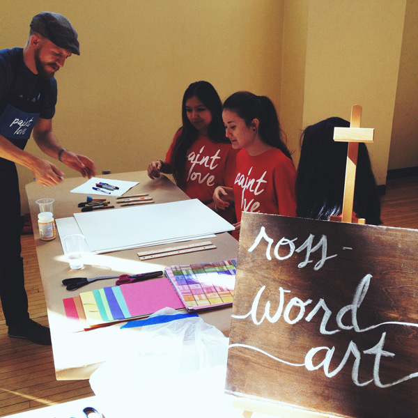 Paint Love Artists Ross Boone teaching the technique to GSU volunteers.