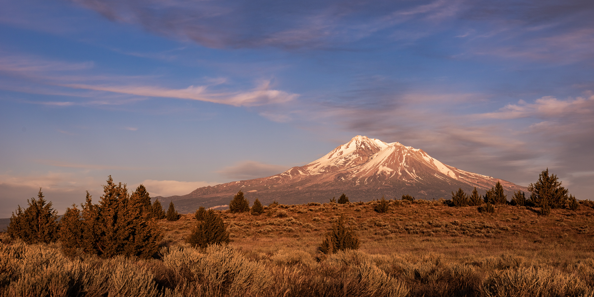 Mt. Shasta bathing in golden, glorious light a few minutes before sunset.
