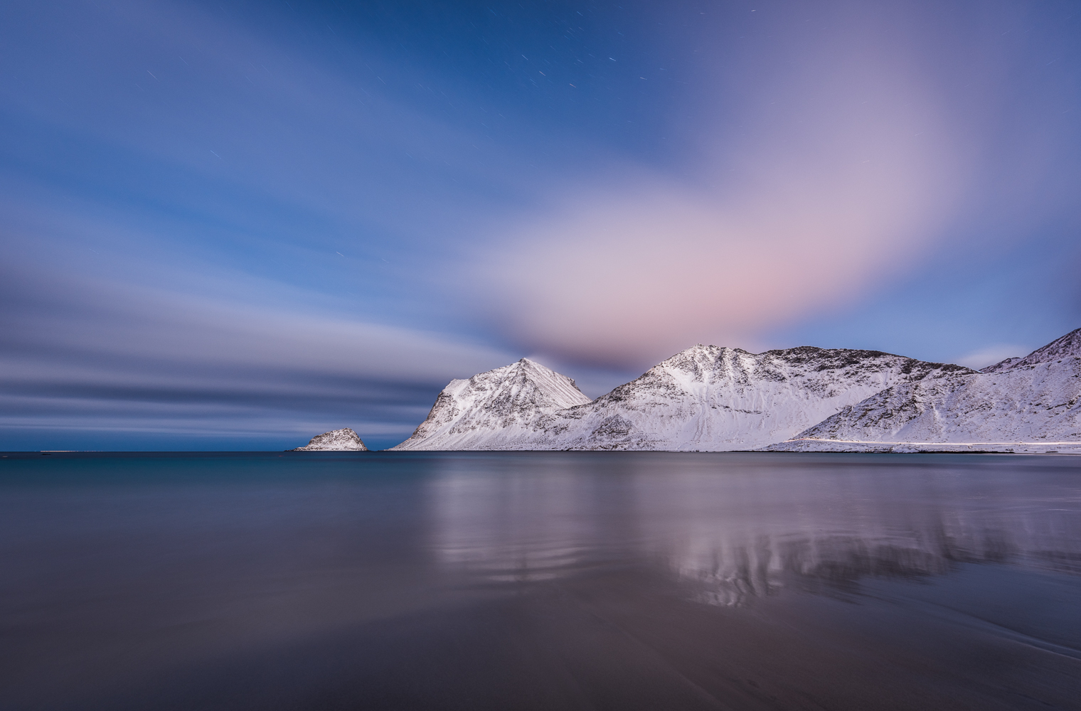 A long exposure at night reveals the most characteristic features of the beach of Vik, Lofoten, because ephemeral elements like the surf are mitigated.
