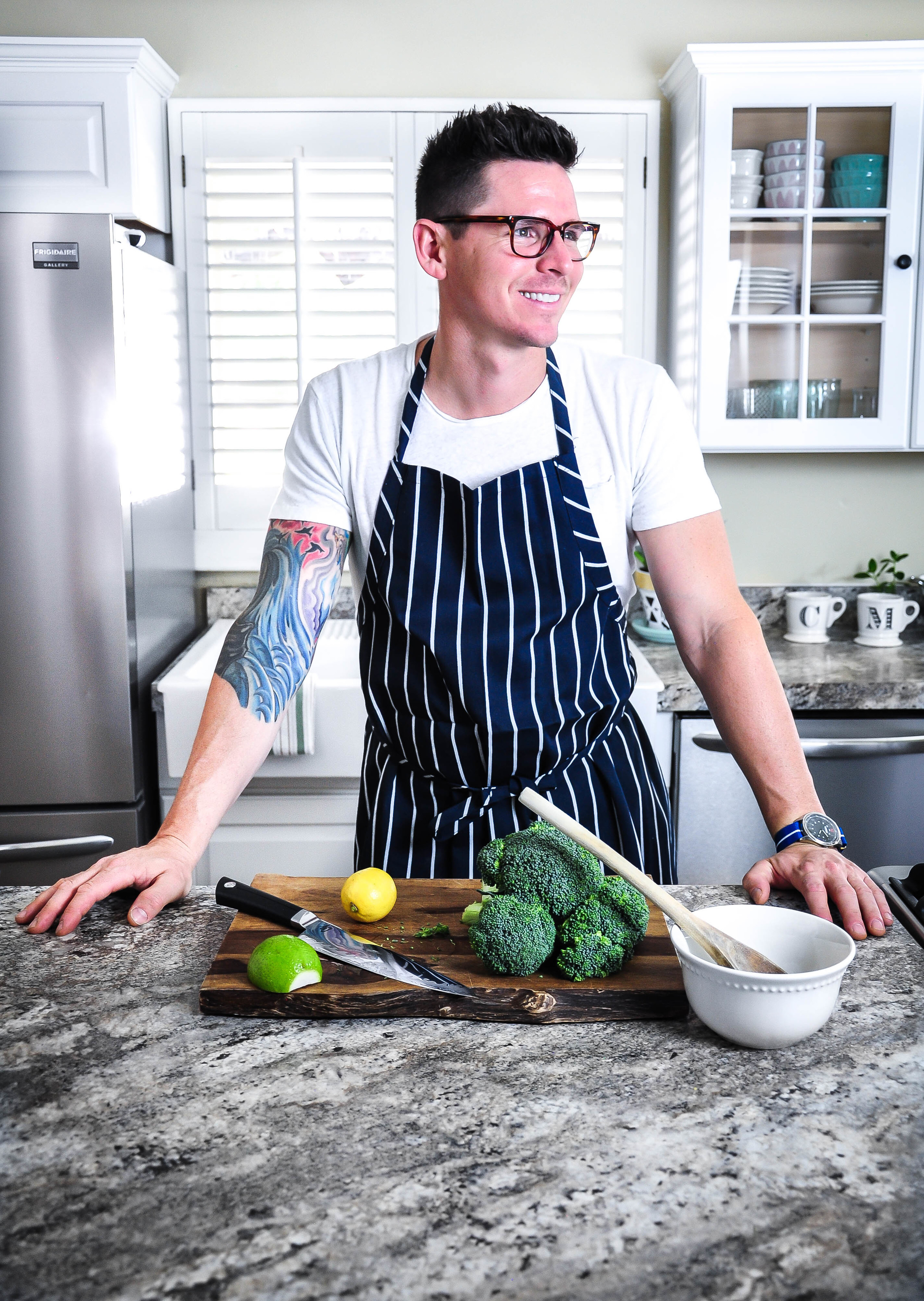 man in apron cooking in remodeled kitchen