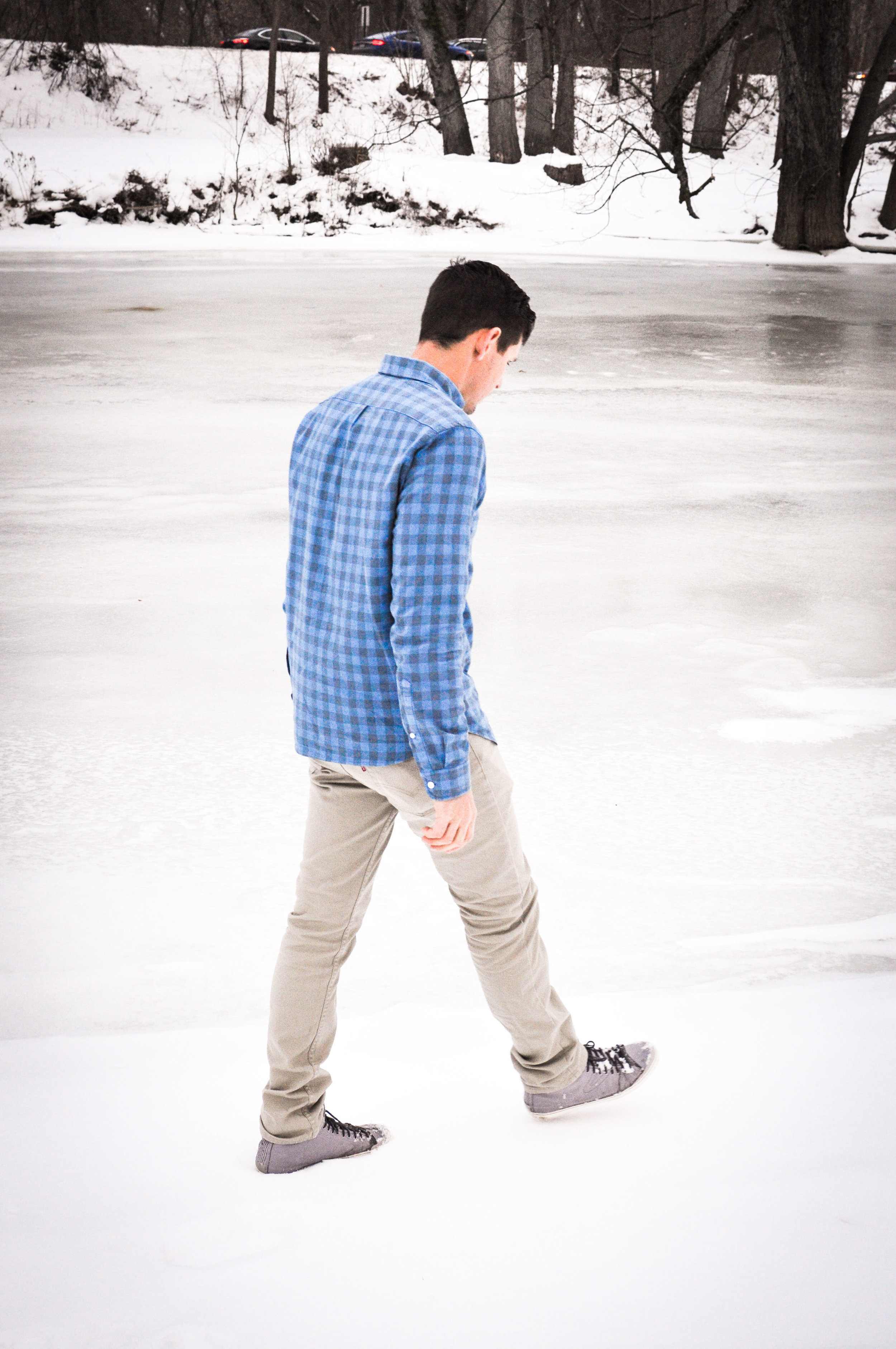 Man in blue shirt walking in snow