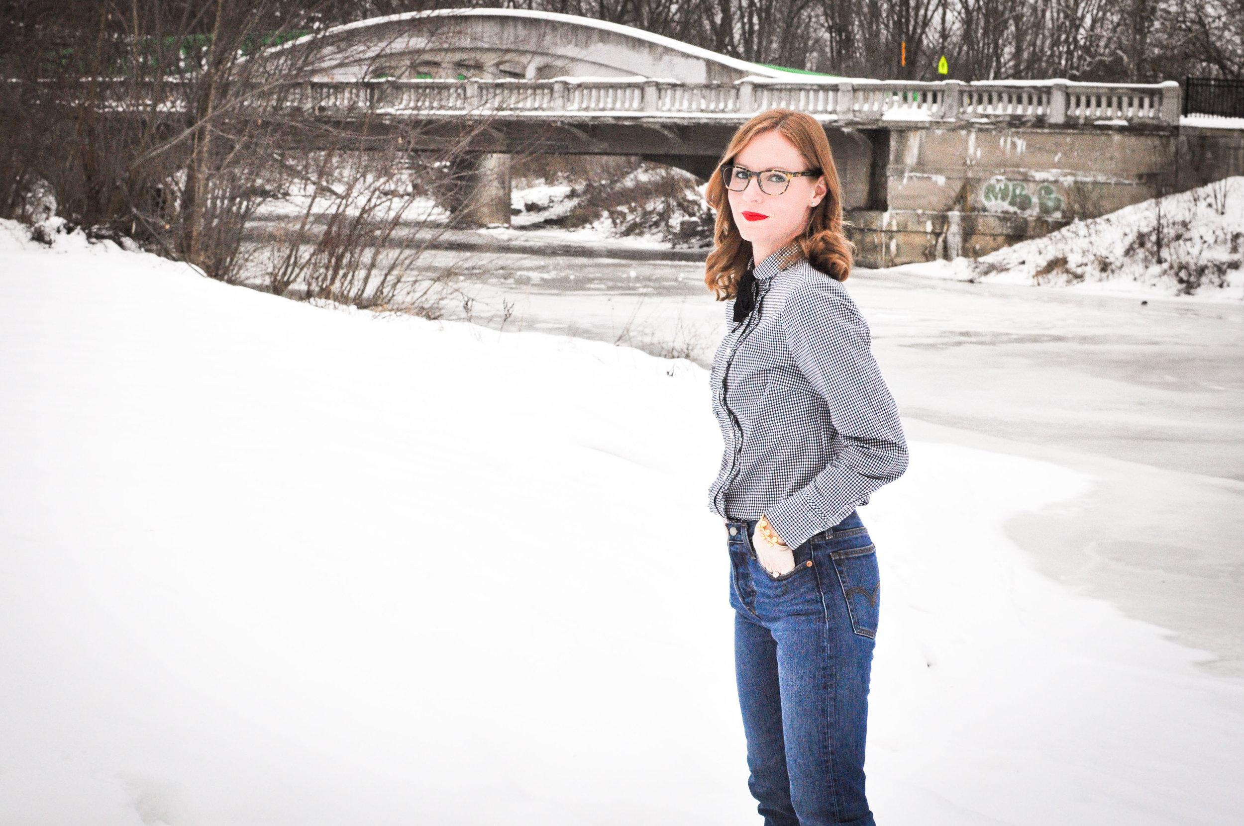 Woman in jeans in front of snowy bridge