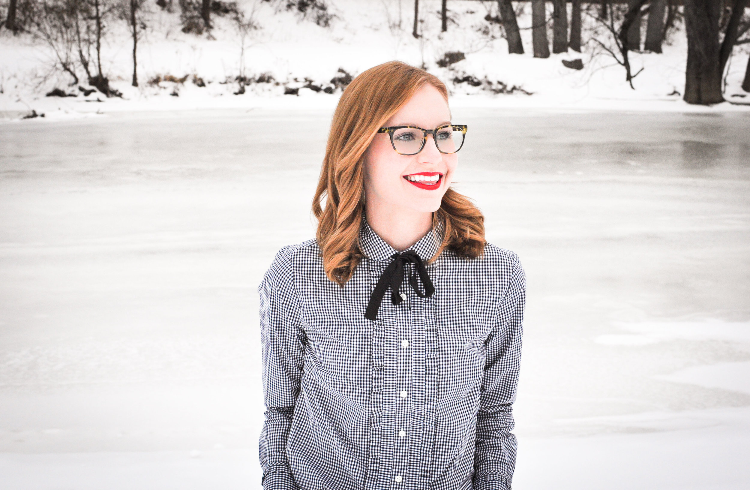 woman with red lipstick and glasses in snow