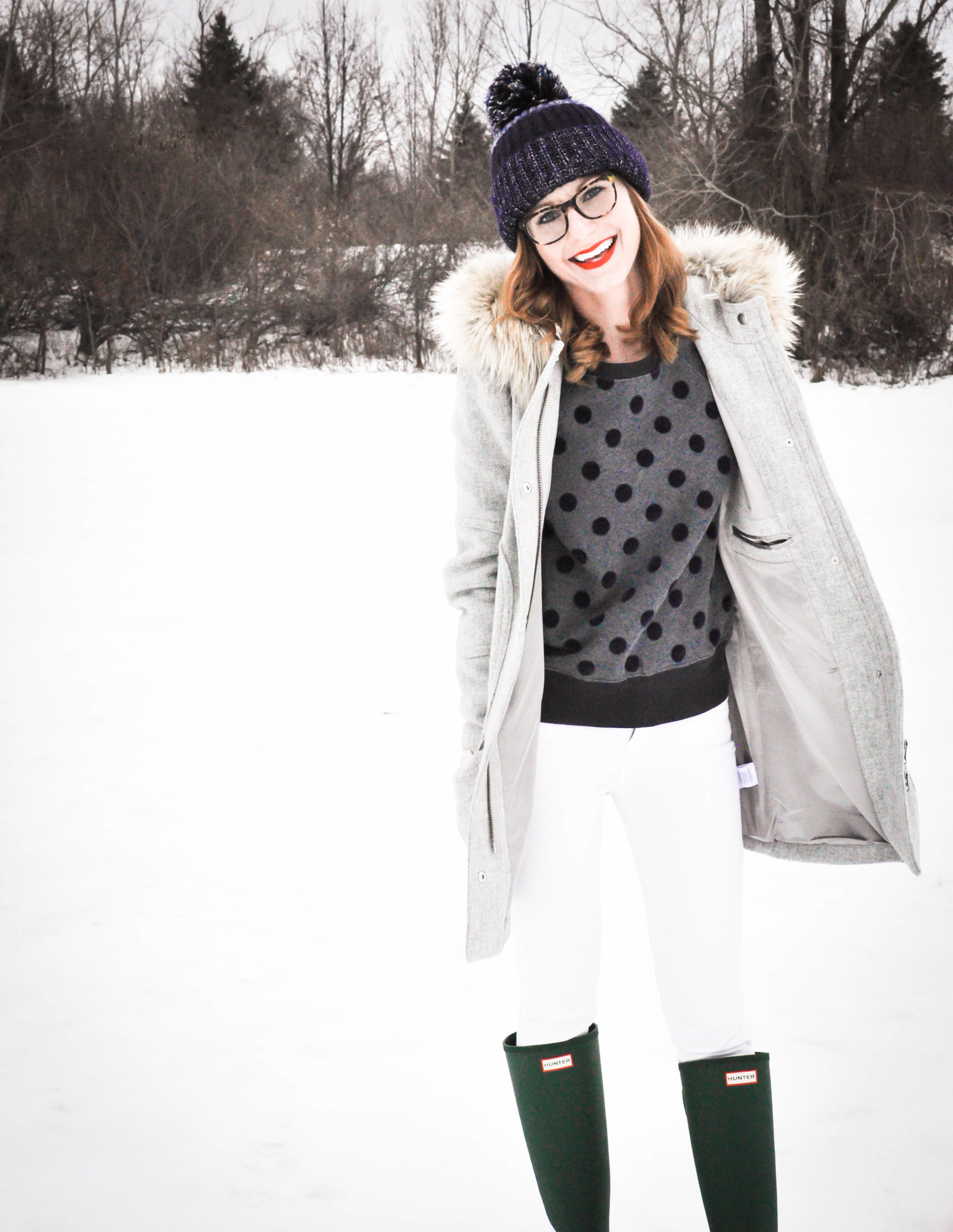 Woman in winter clothes in snow smiling at camera