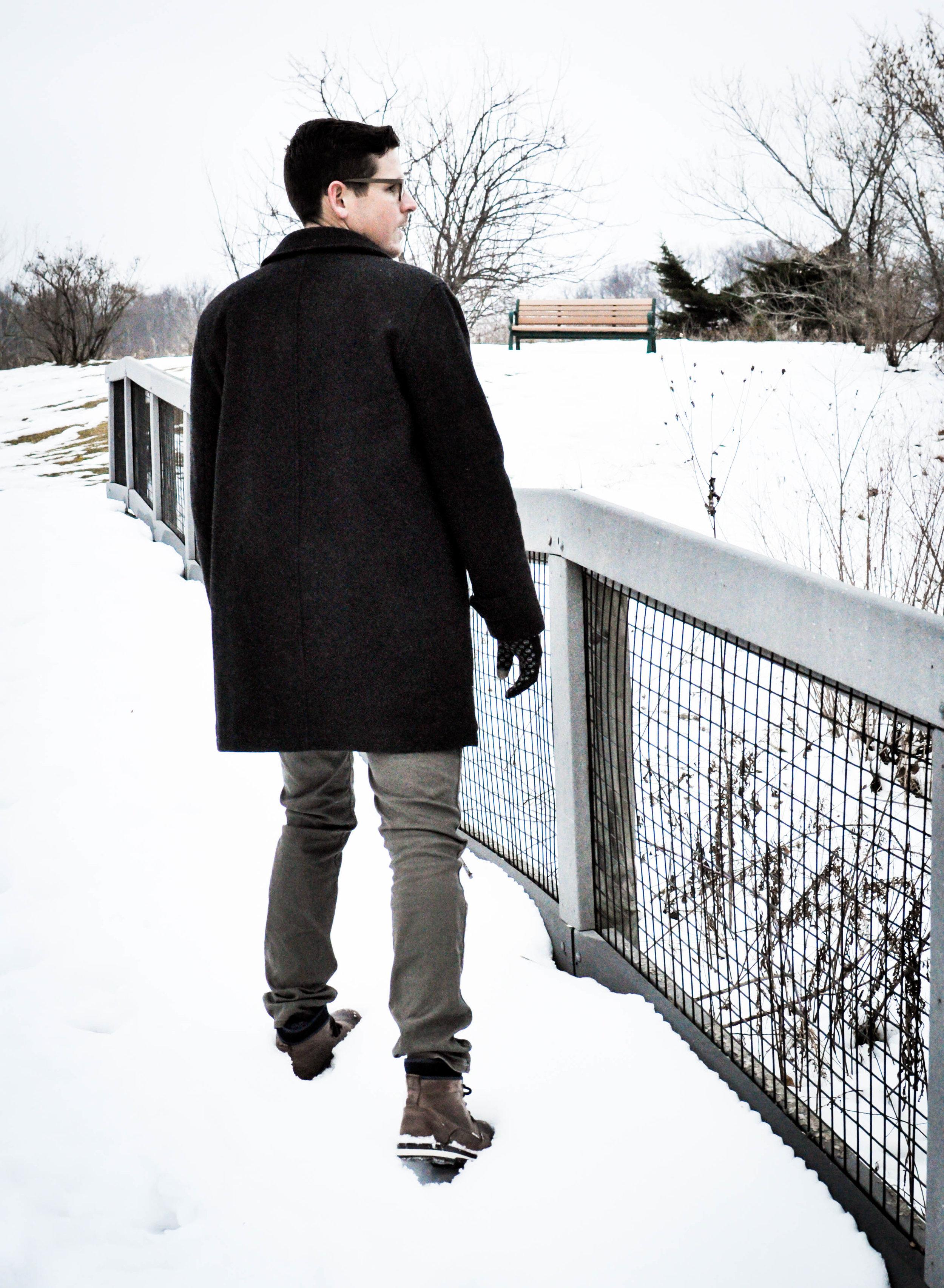 Man in black coat walking in snow