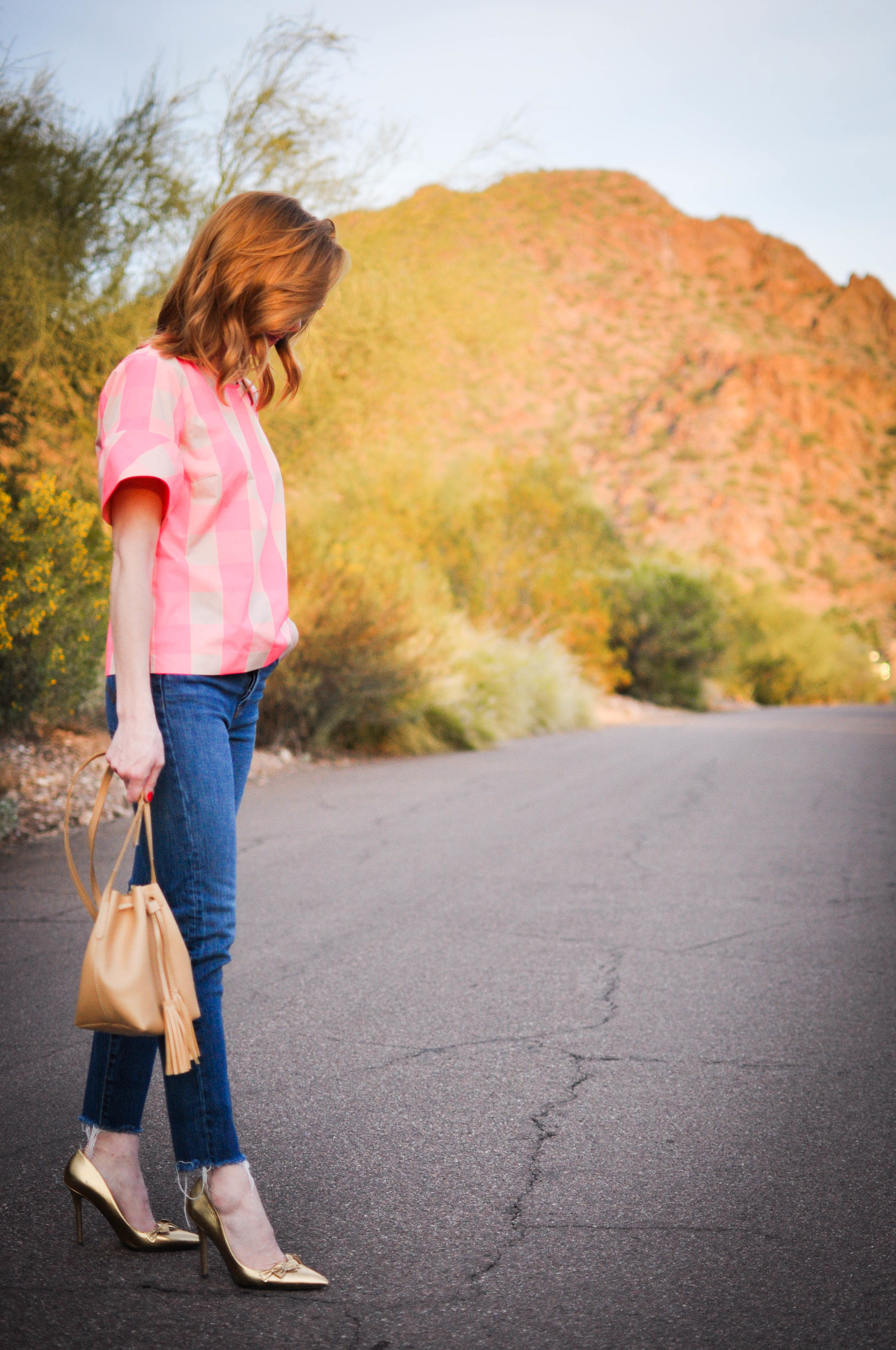 woman in pink top and jeans crossing desert road