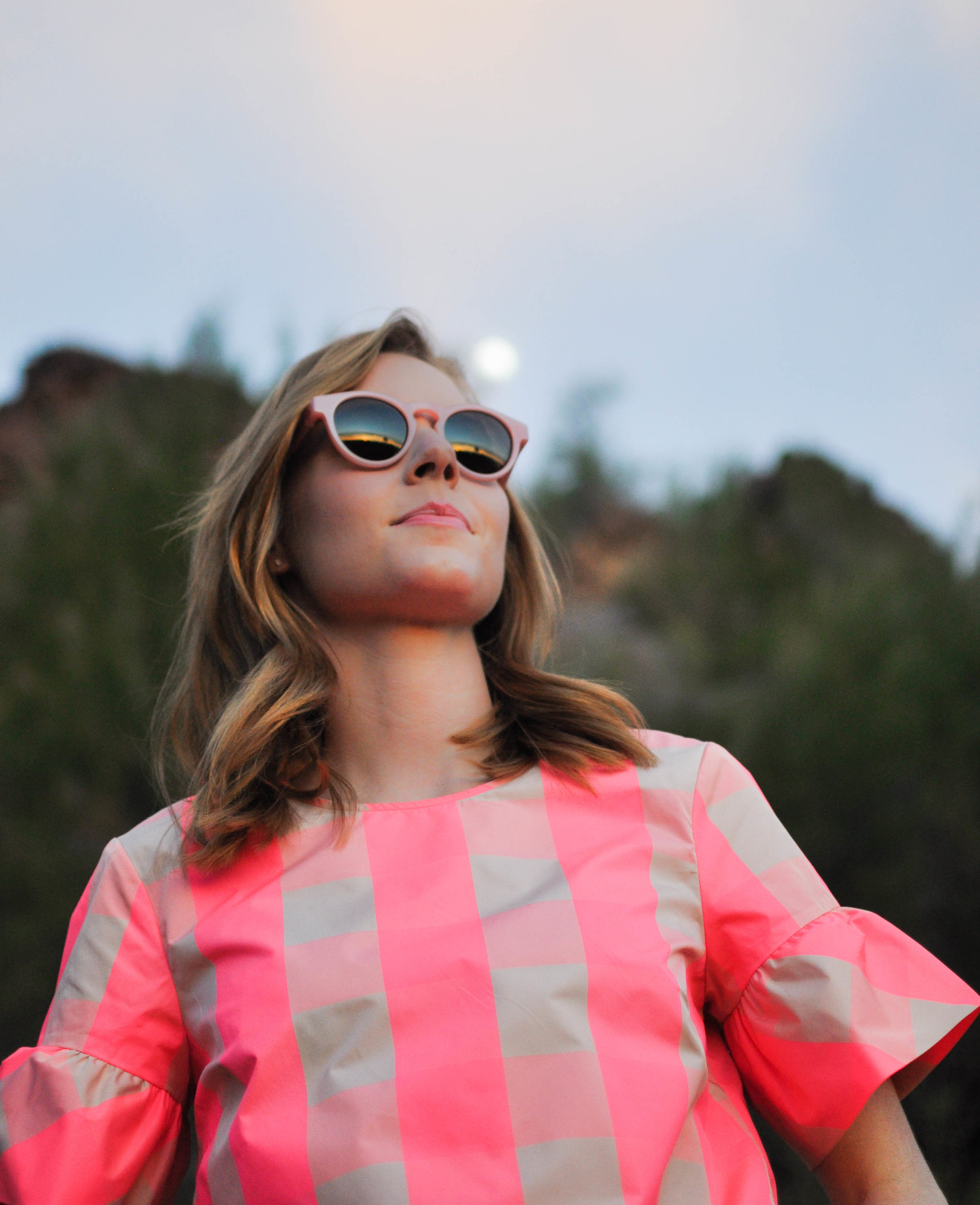 Woman in sunglasses and pink top at sunset