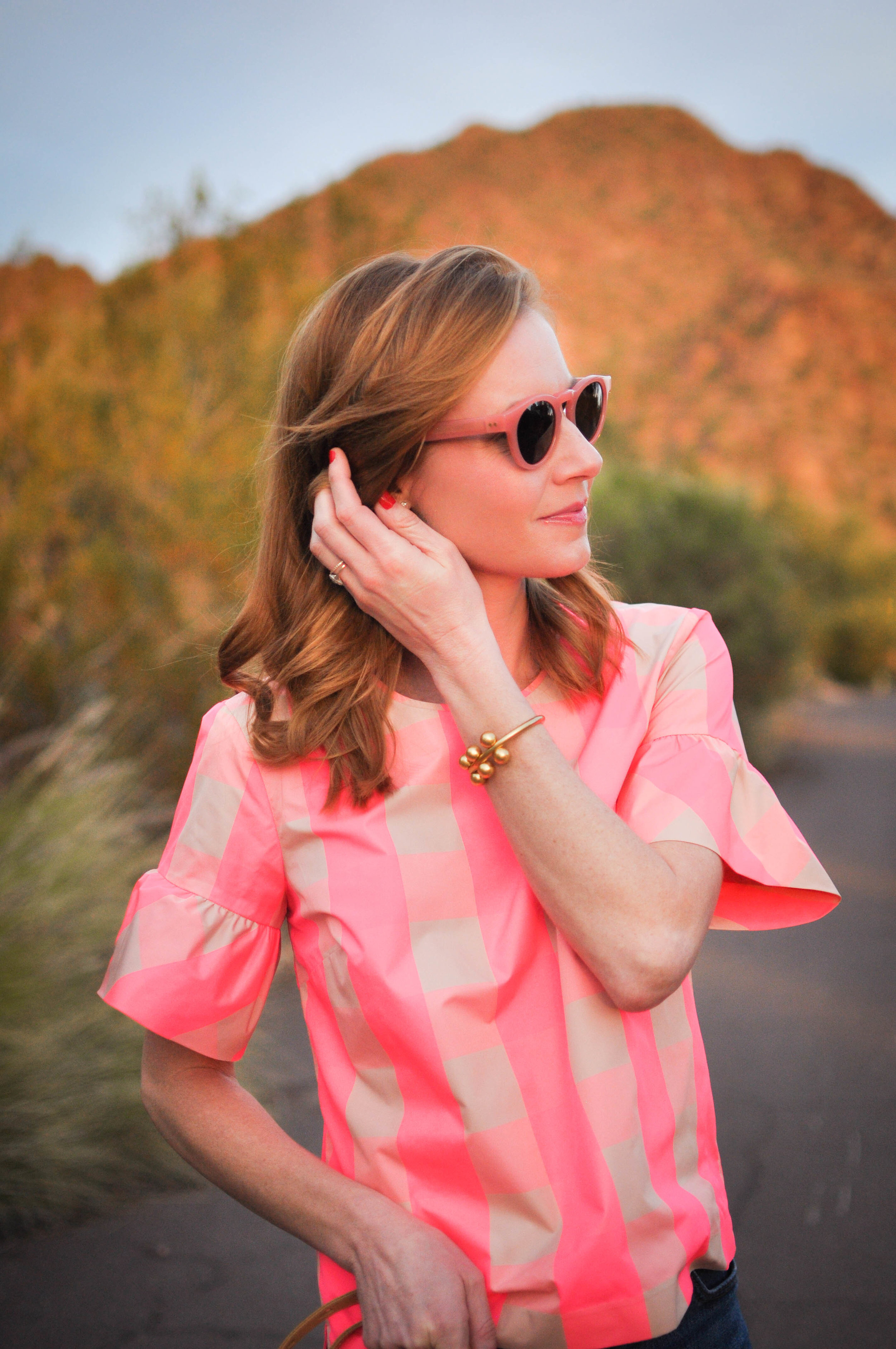 Woman in pink top and sunglasses touching hair