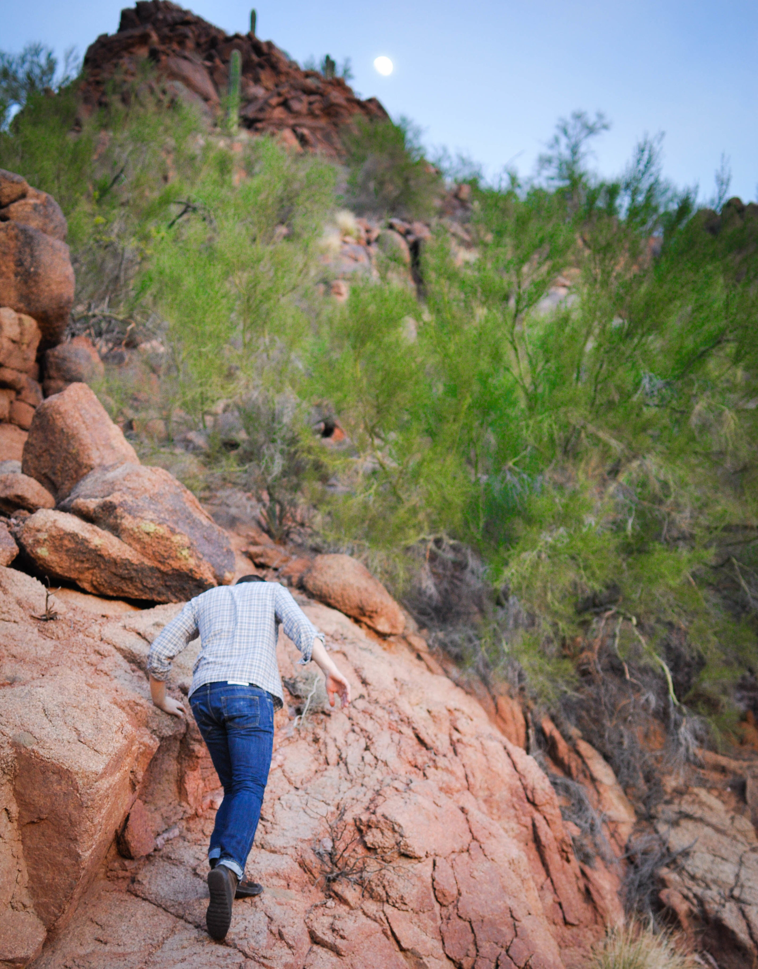 man climbing mountain in jeans
