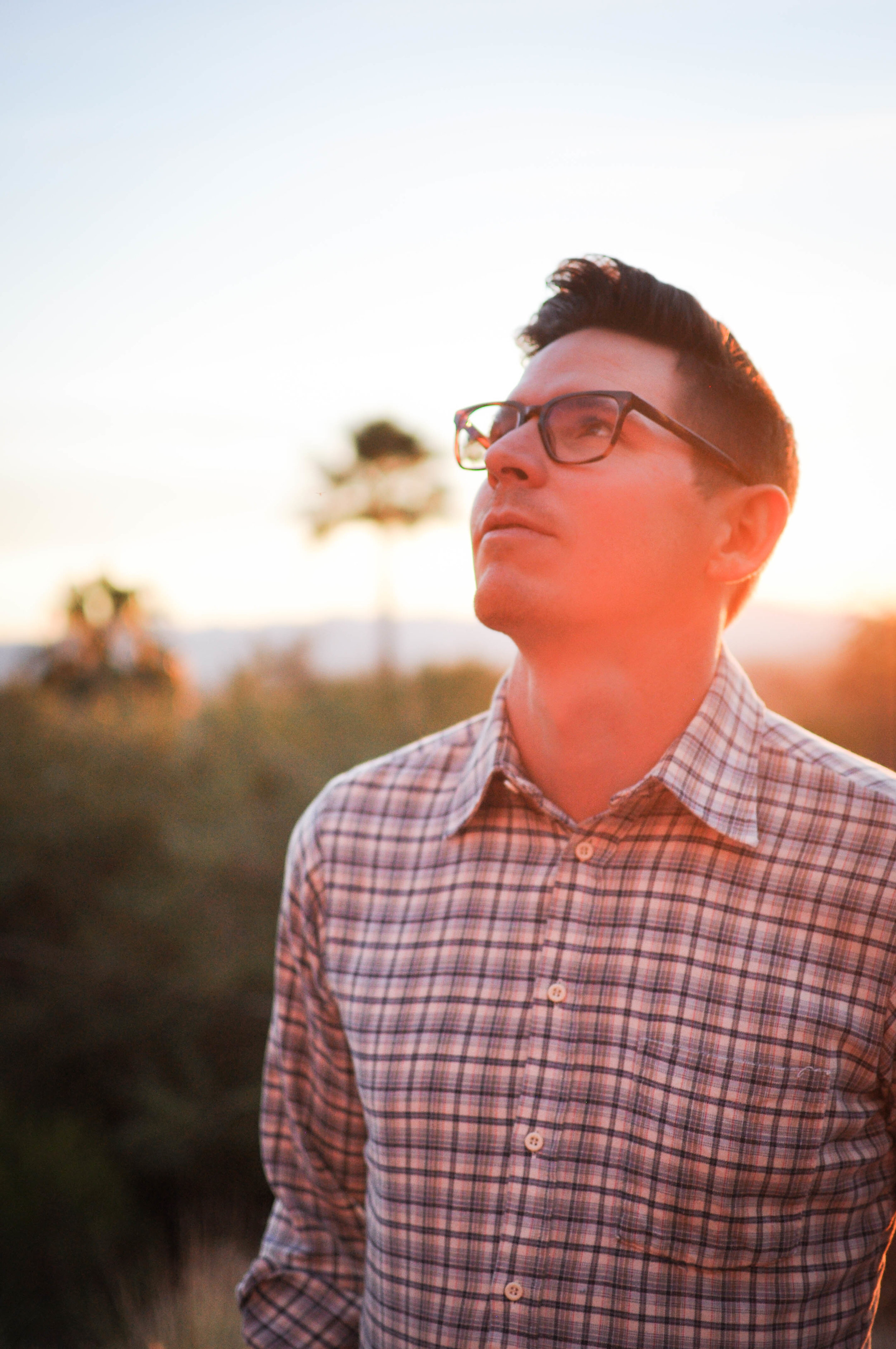 Man in glasses looking up at sunset