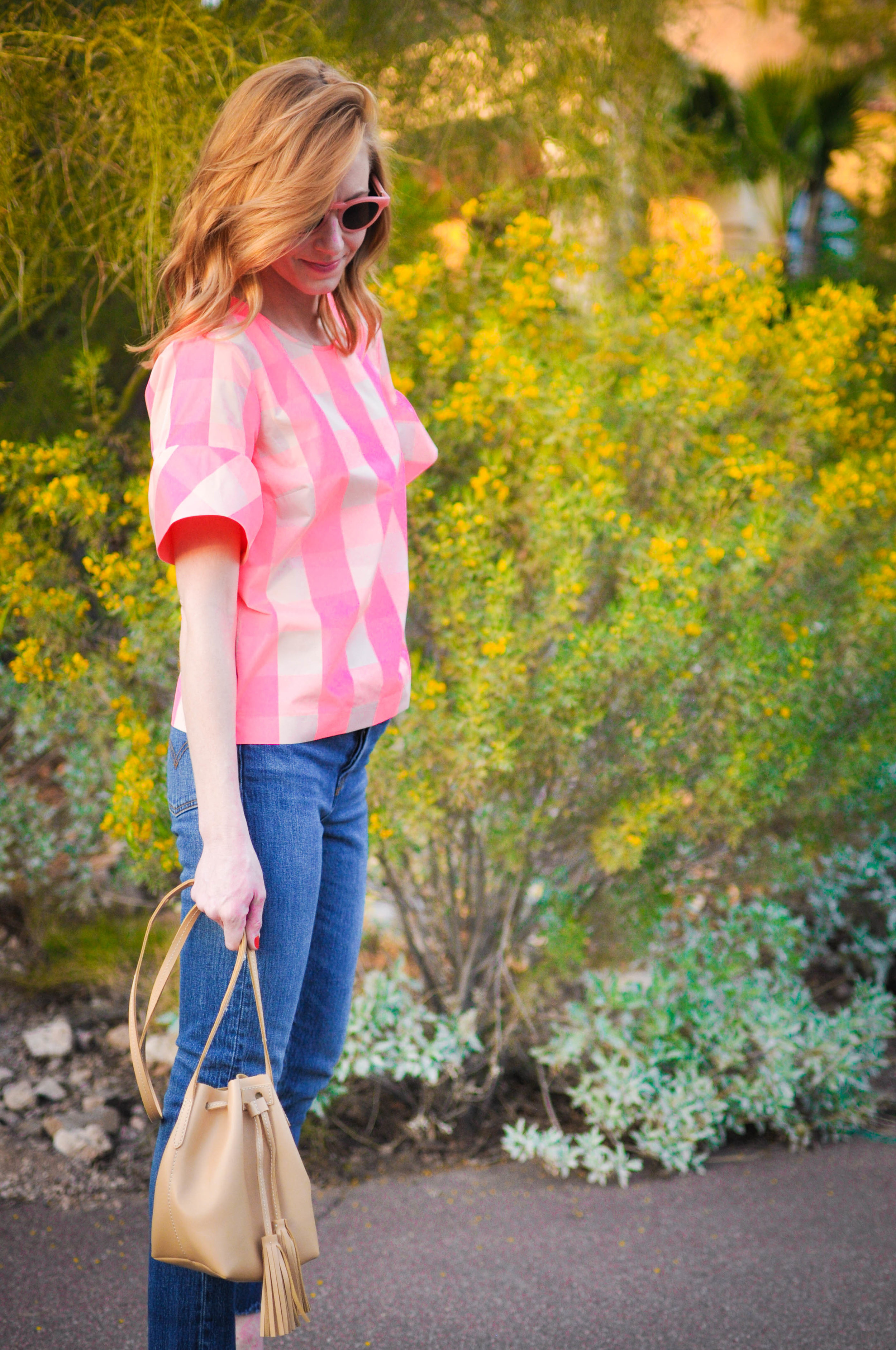 Woman in pink top and jeans at sunset