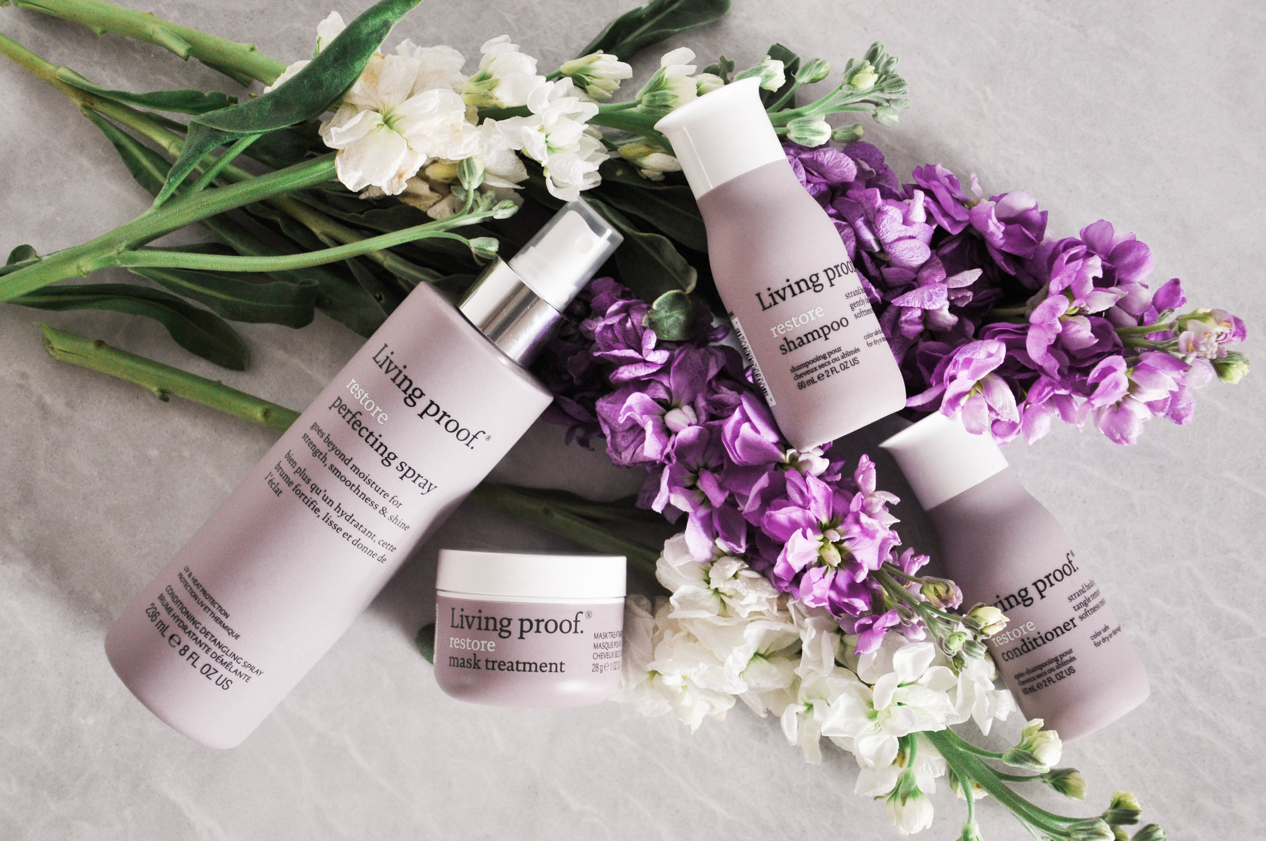 living proof hair products displayed with flowers