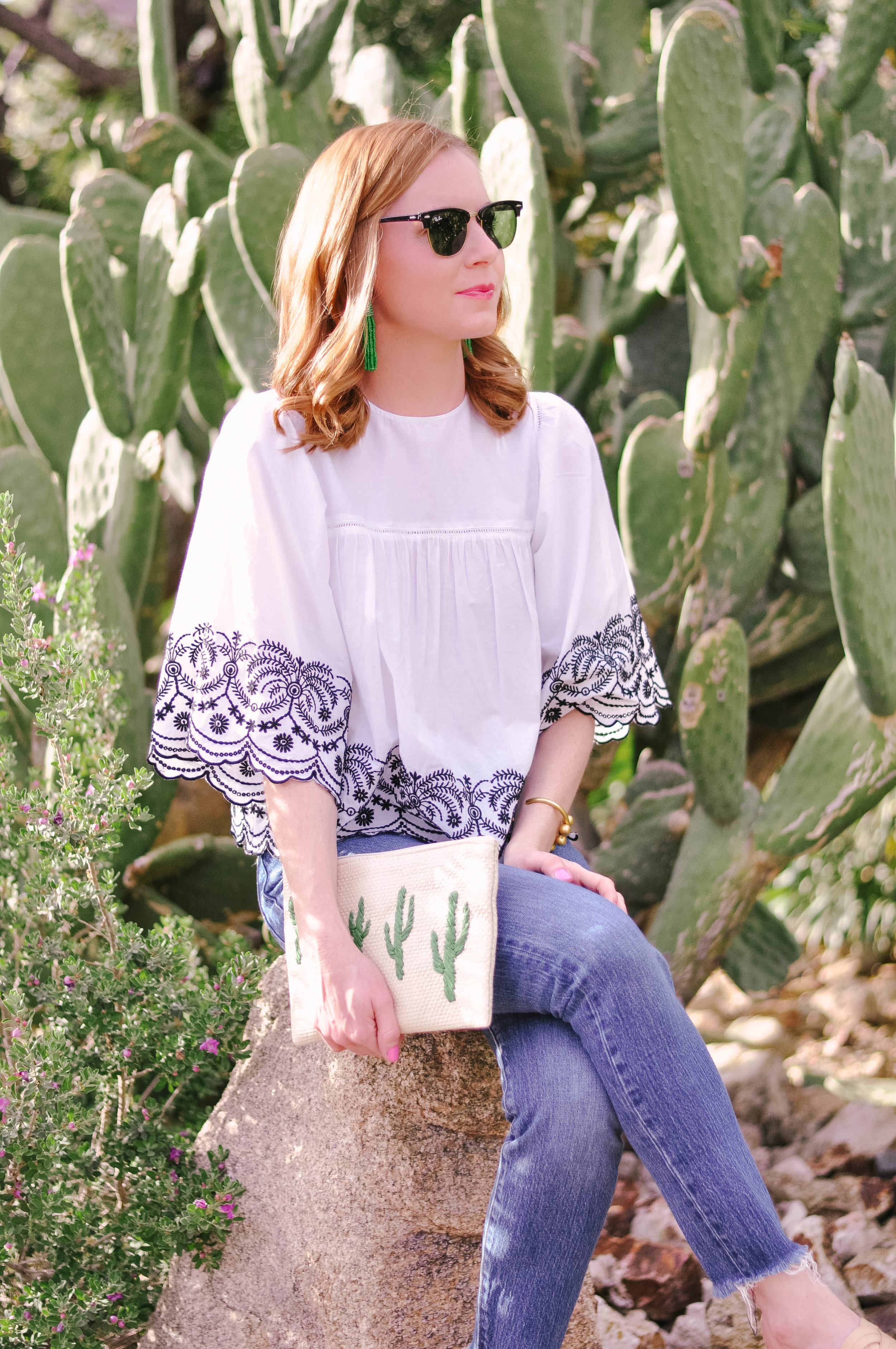 Woman in white top and sunglasses next to cactus