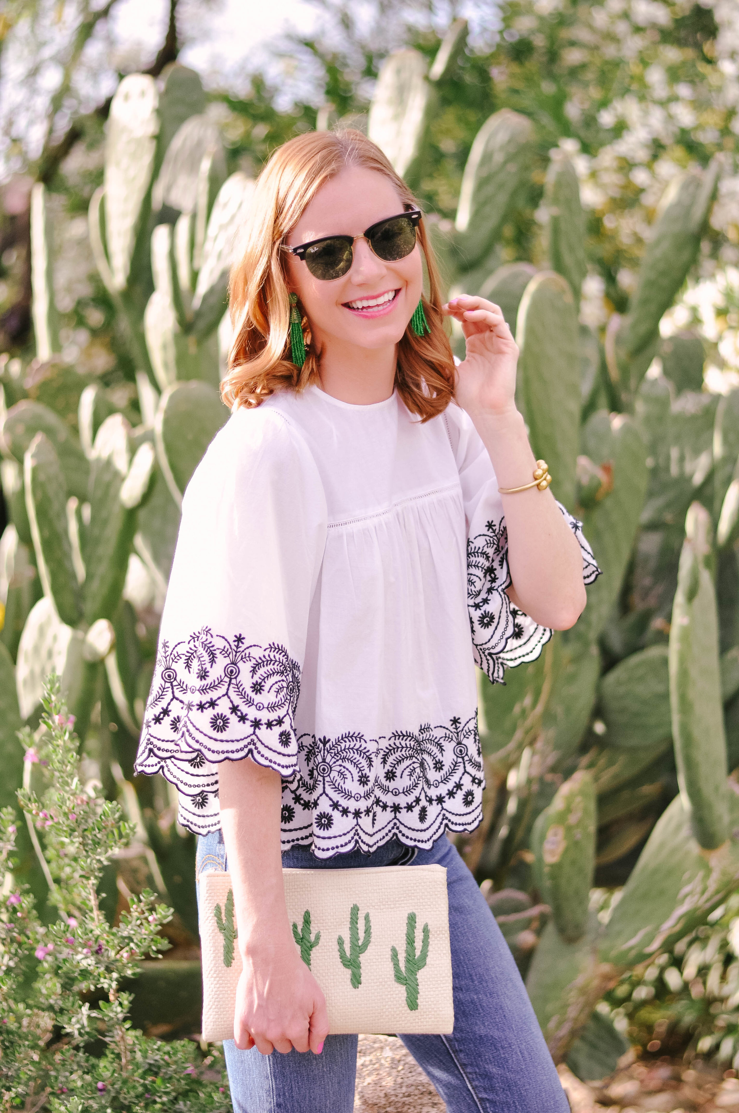 Woman in sunglasses next to cactus