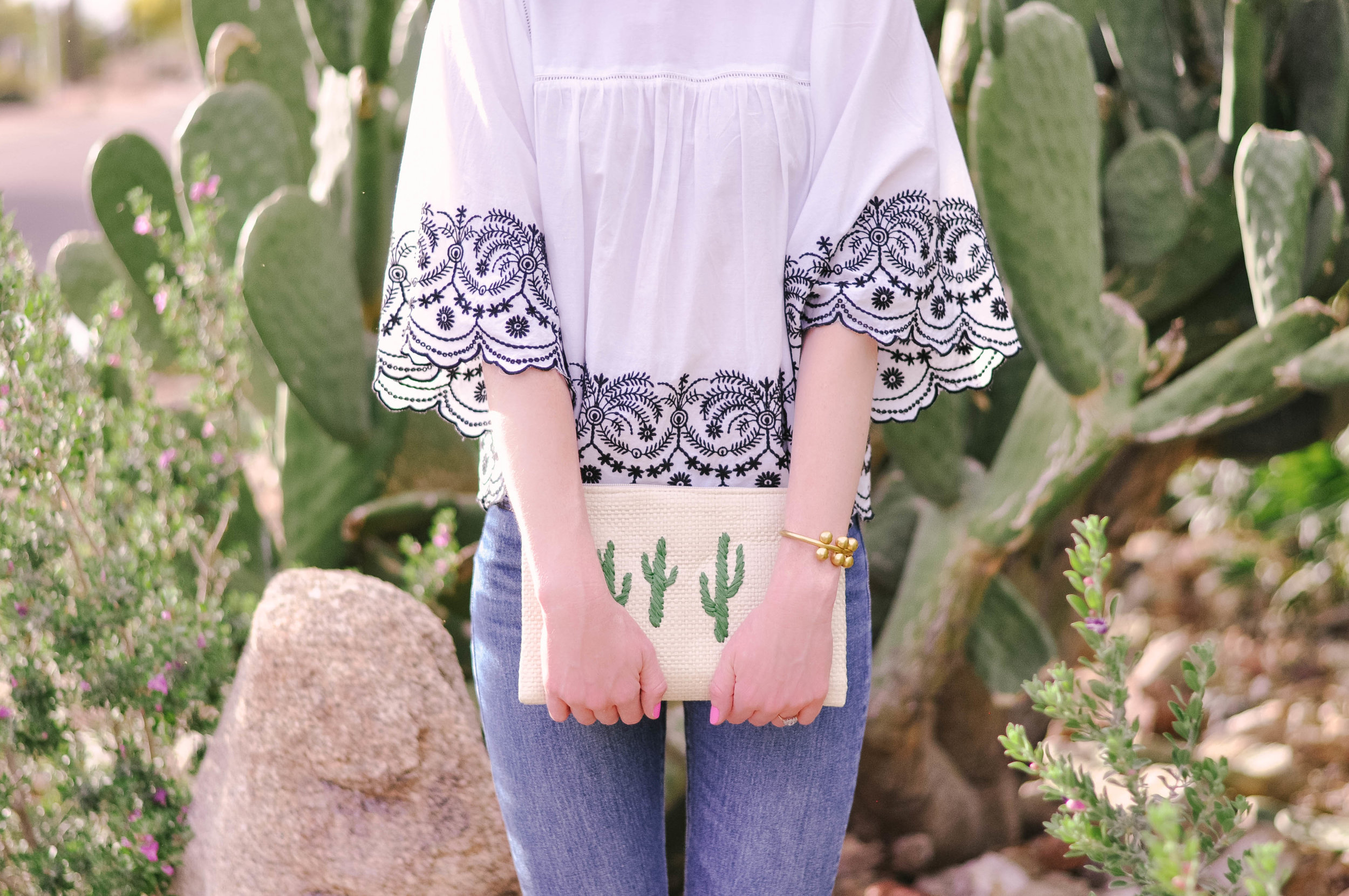Woman in white top and cactus clutch