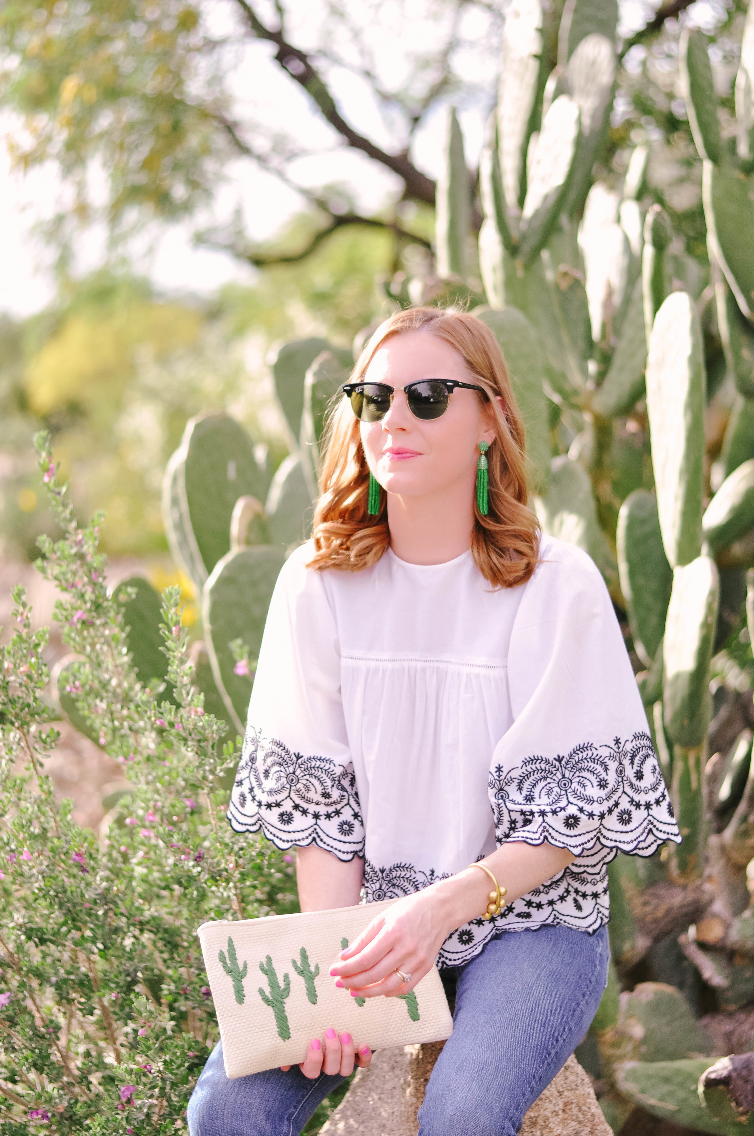 Woman in sunglasses and cactus clutch