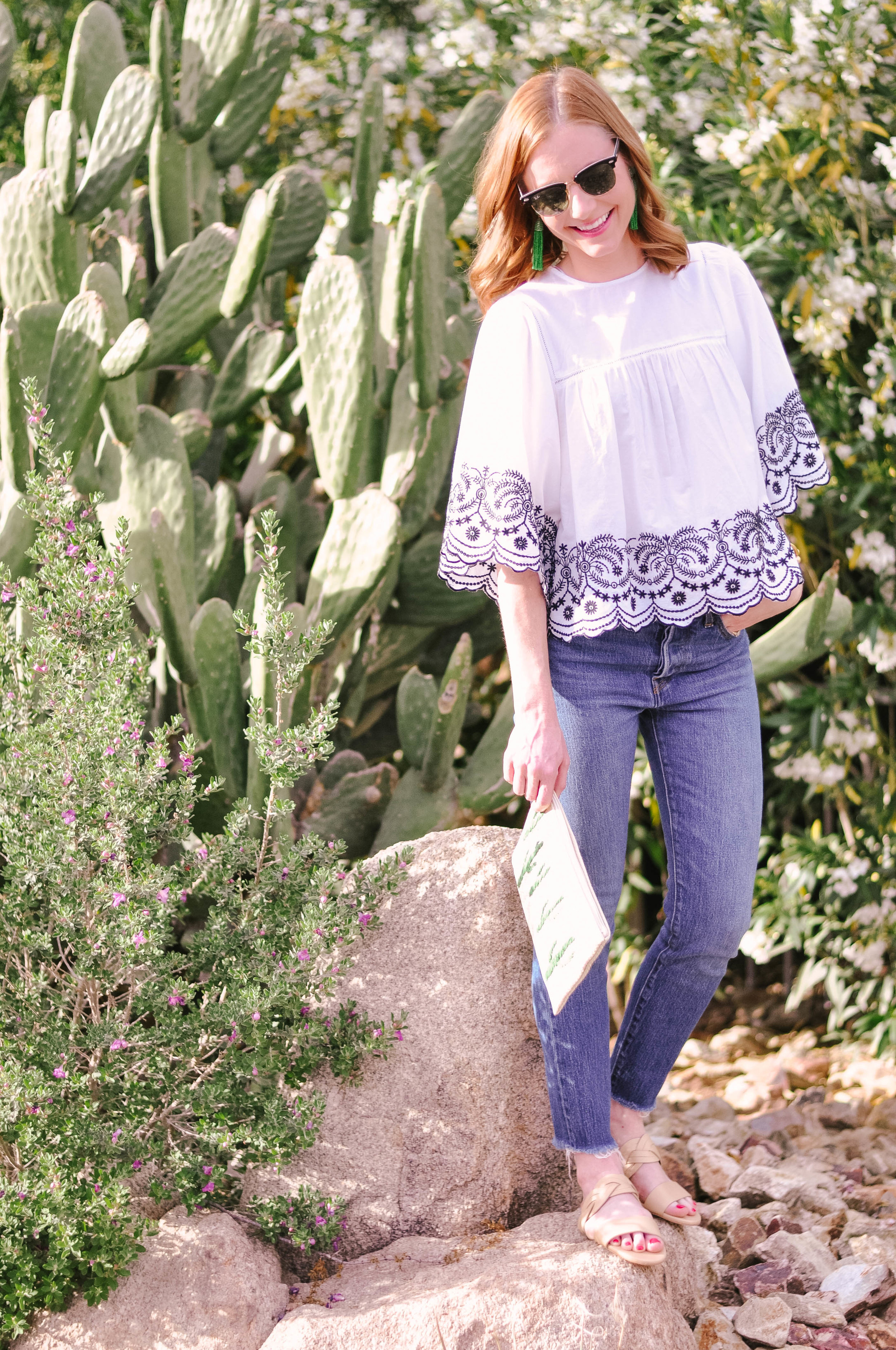 Woman in jeans and sunglasses next to cactus