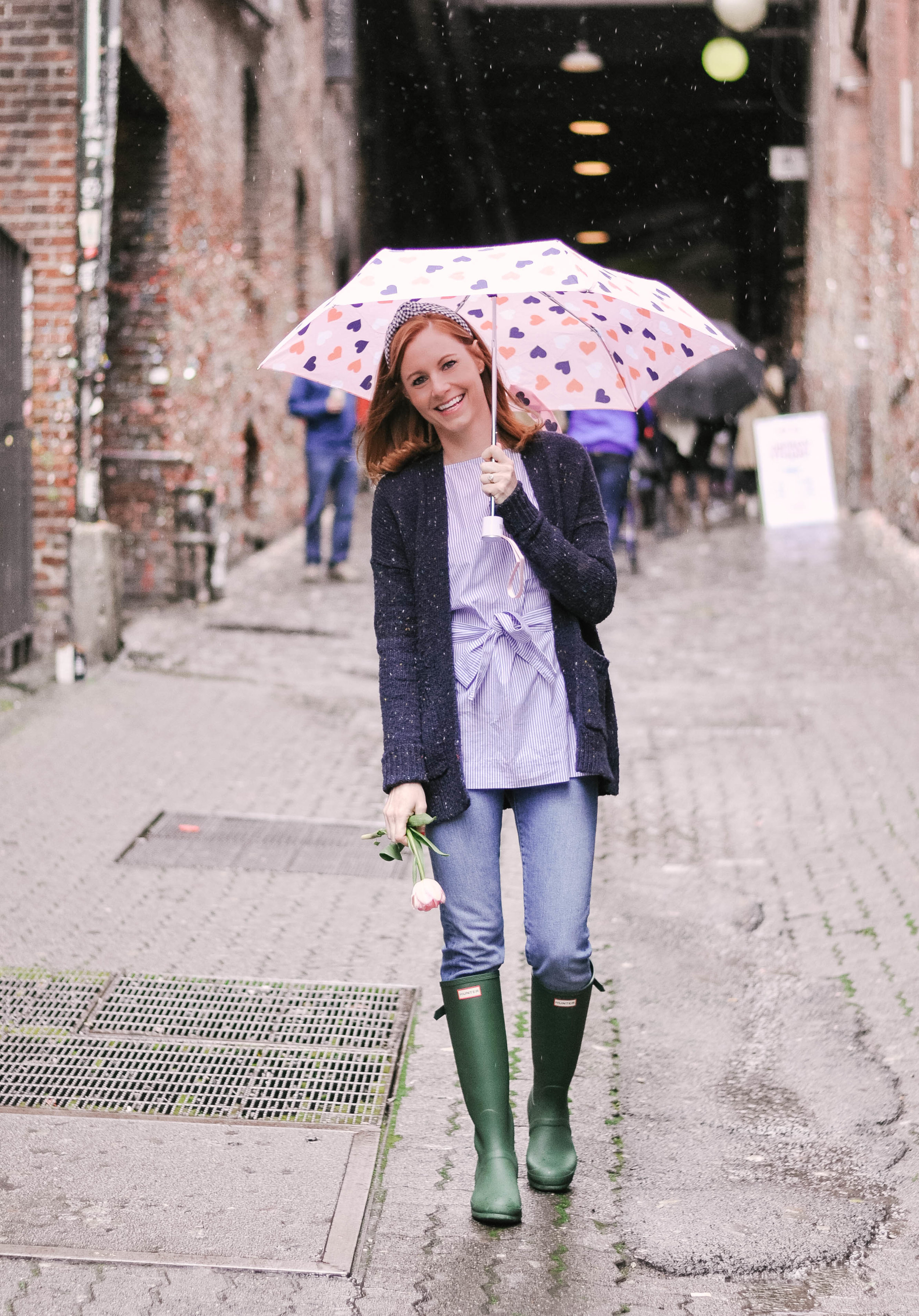 Woman on rainy day with umbrella and boots