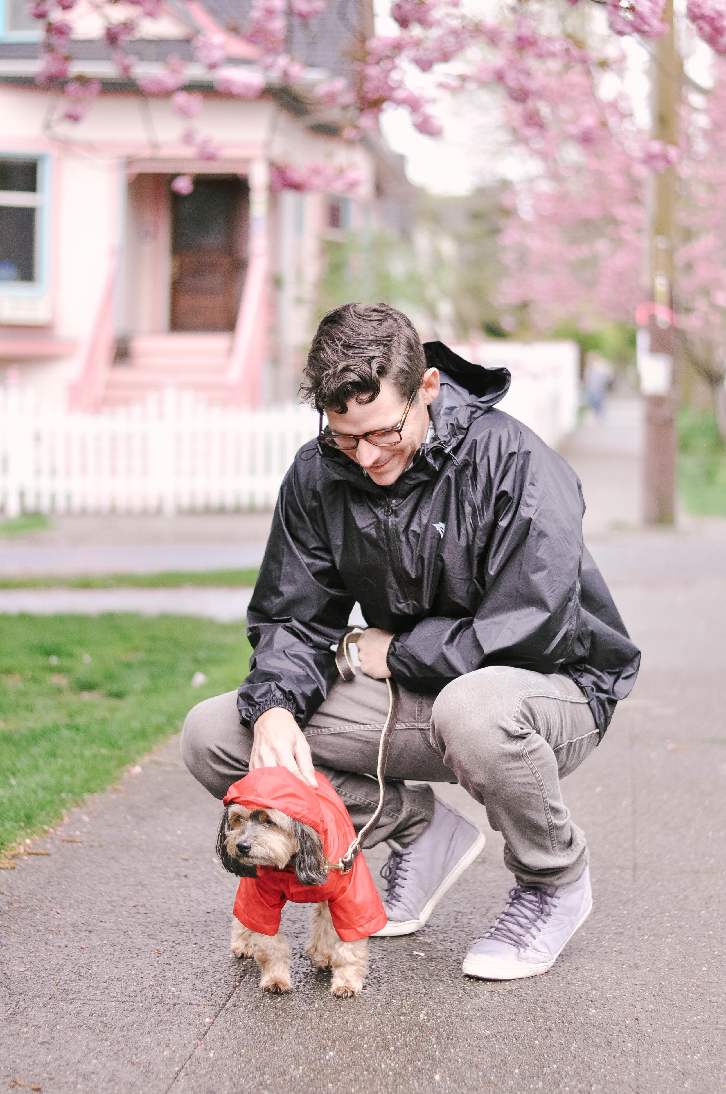 Man bending down to pet dog in raincoat