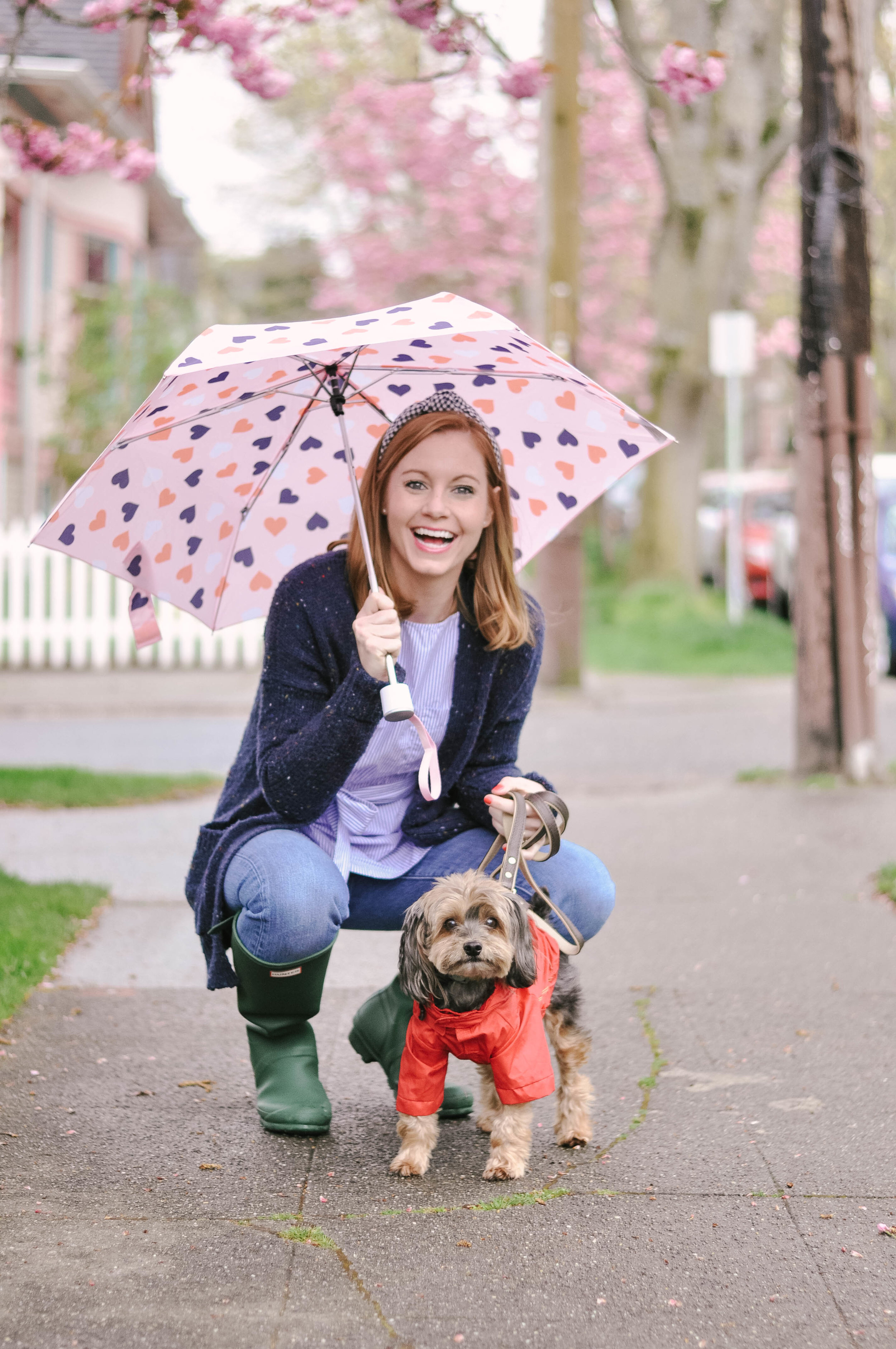 Woman posing with dog in raincoat on rainy day