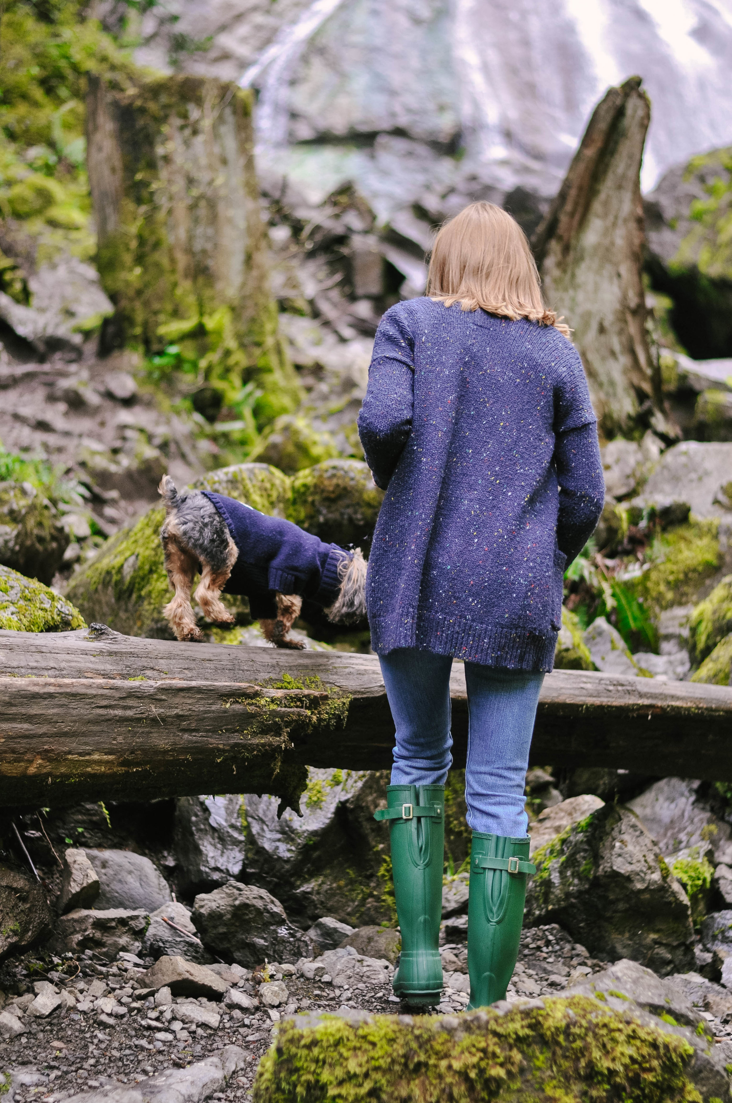 Woman hiking in rubber boots with small dog