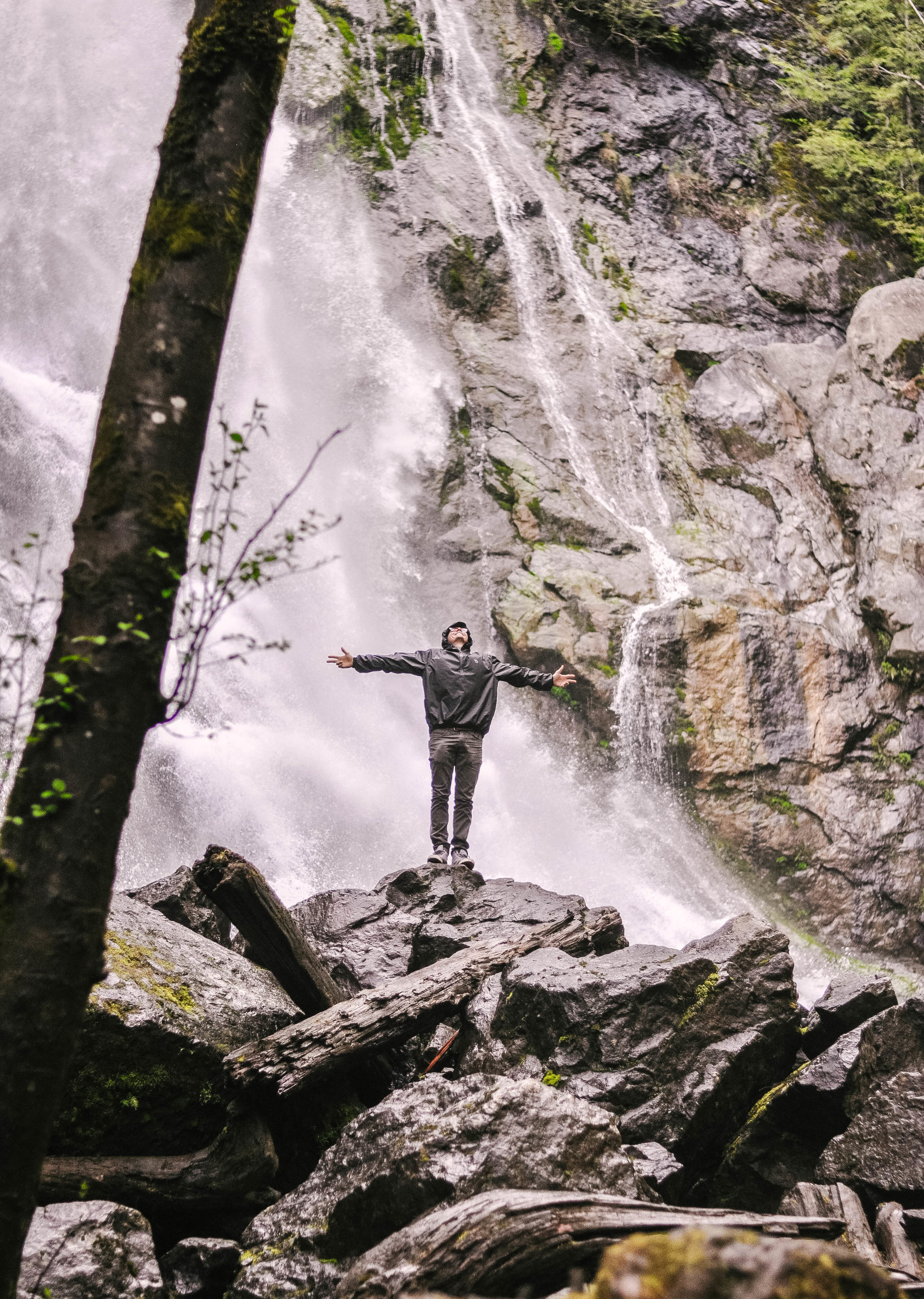 main in raincoat in front of waterfall
