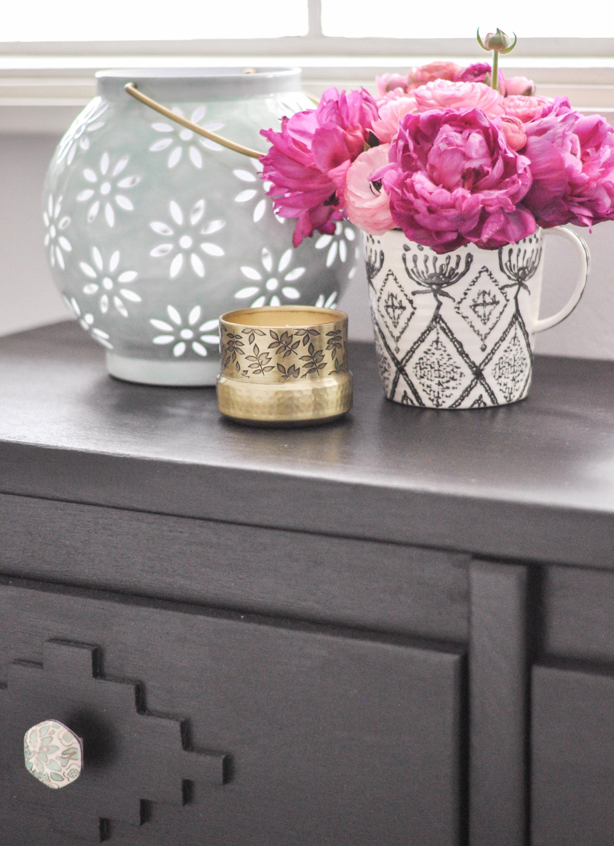 styled dark wood dresser with pink flowers
