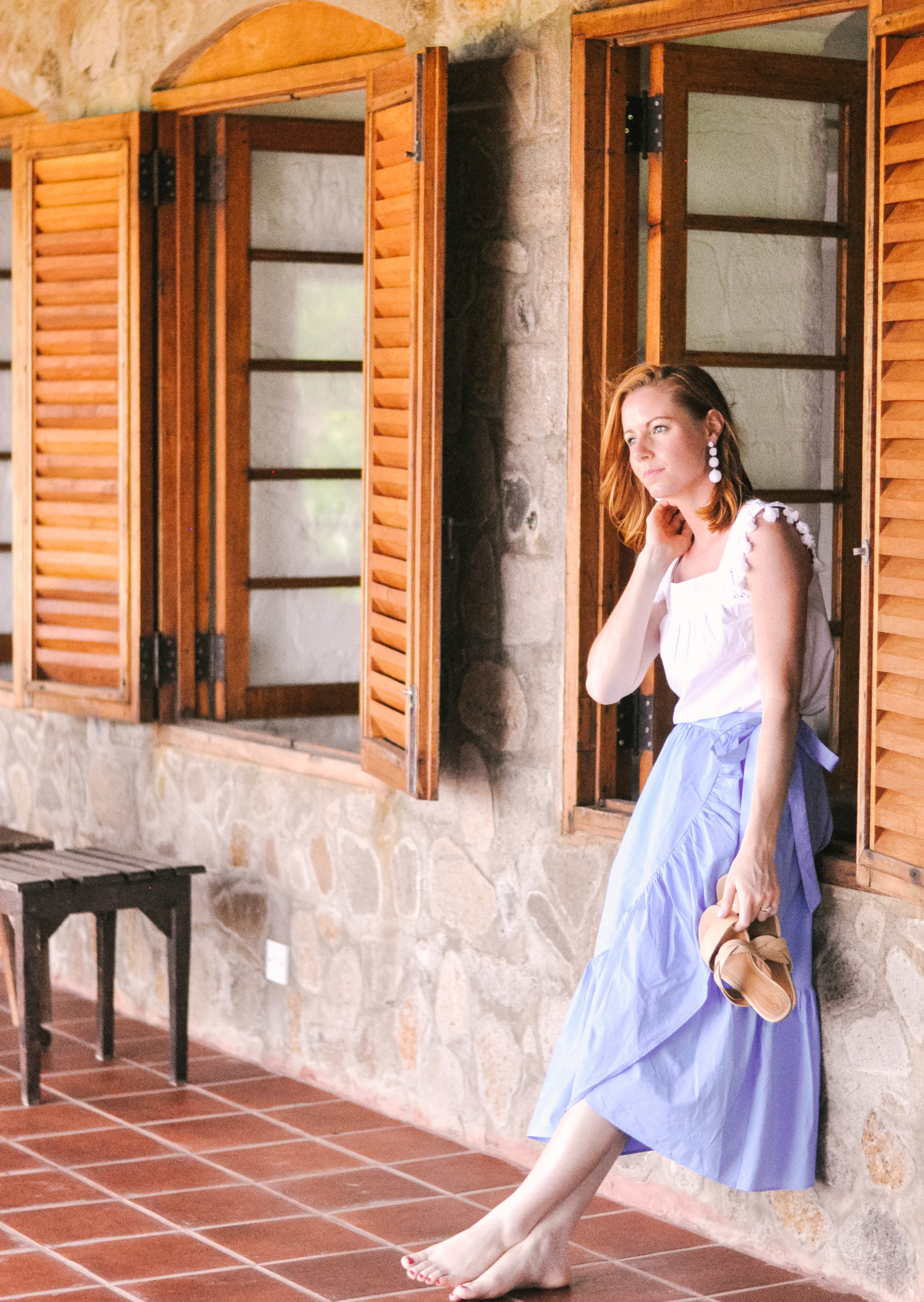 Woman posing against wooden shutters