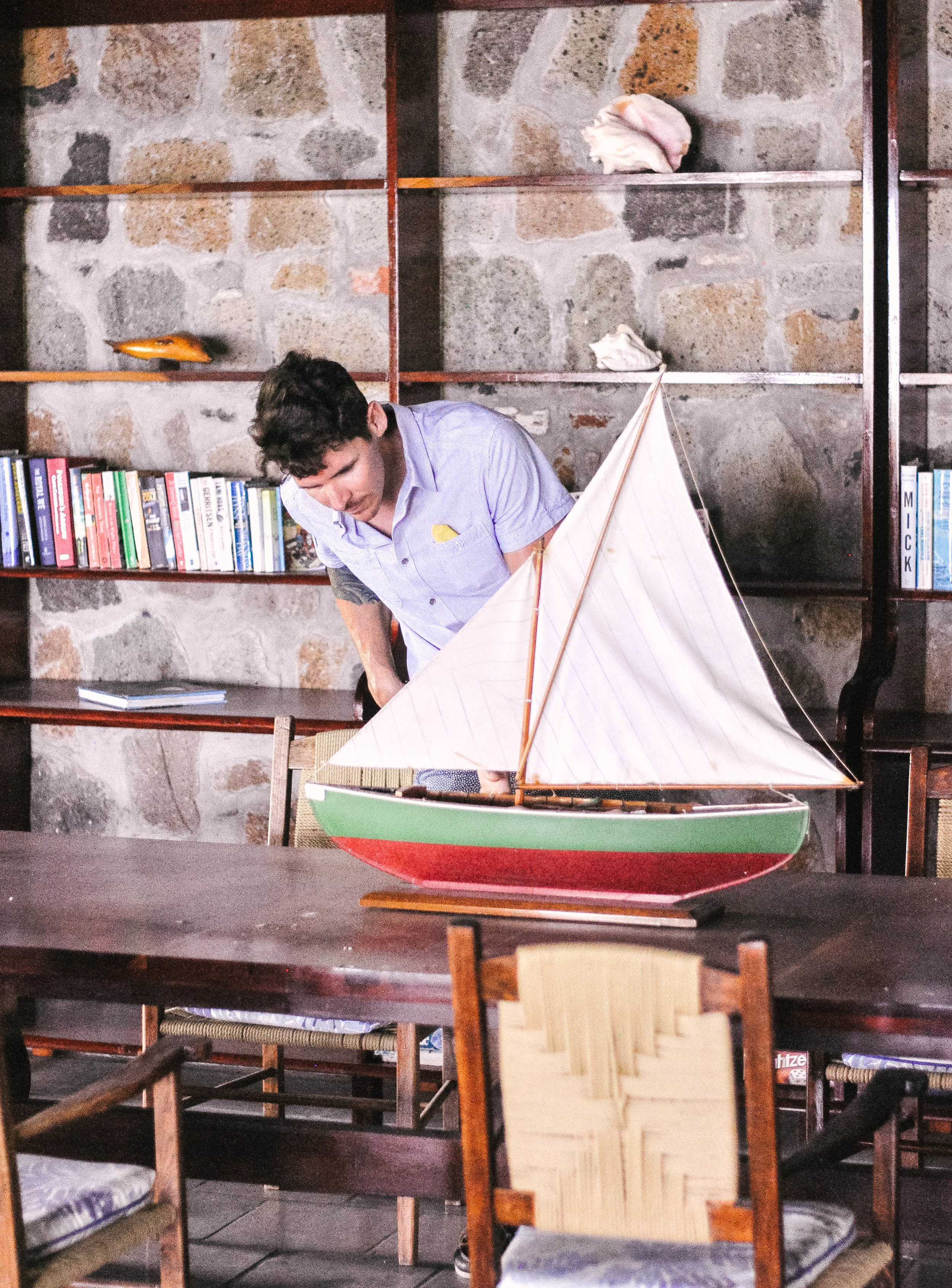 Man looking at model sailboat