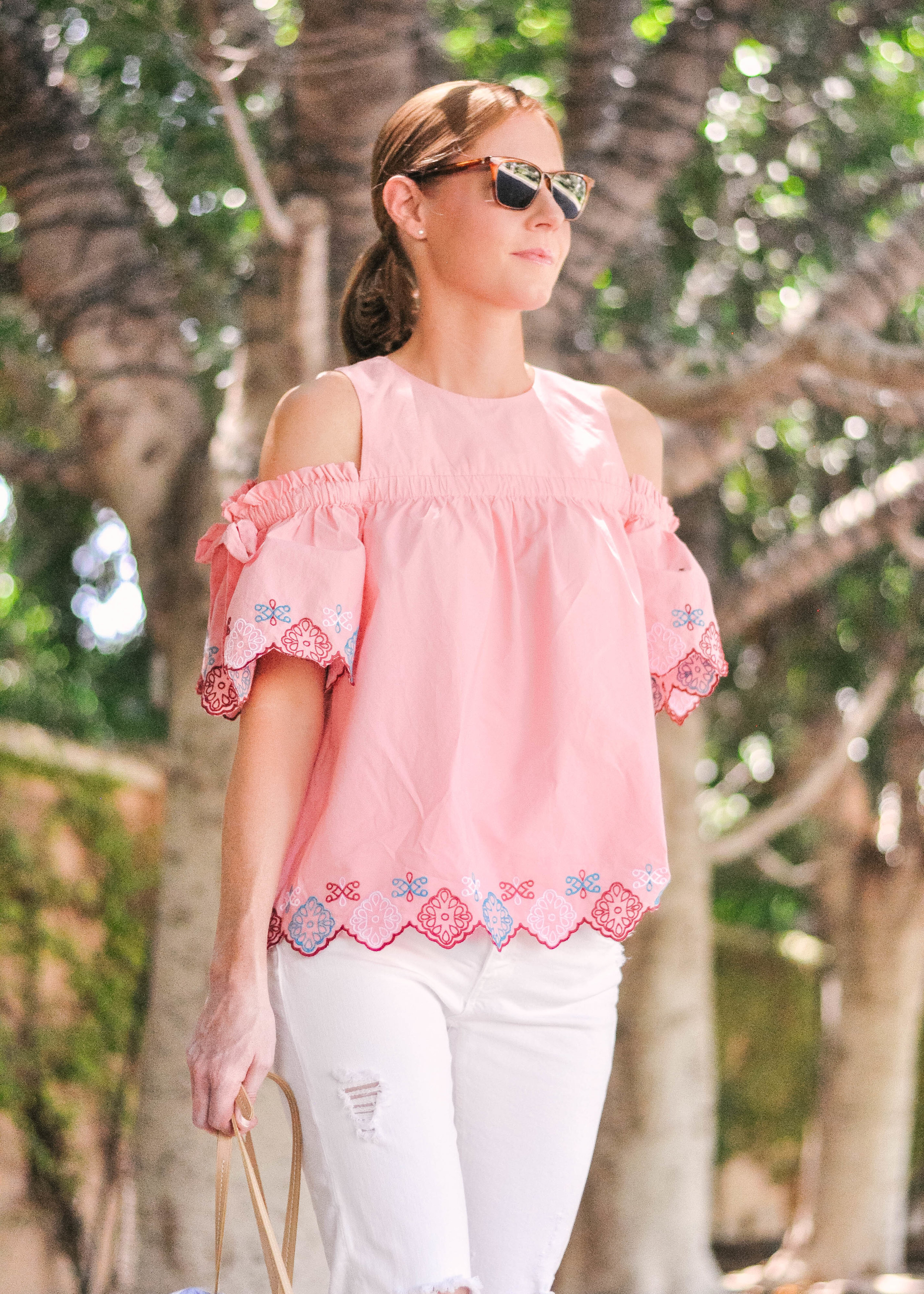 woman in pink Loft top and white jeans in the summer