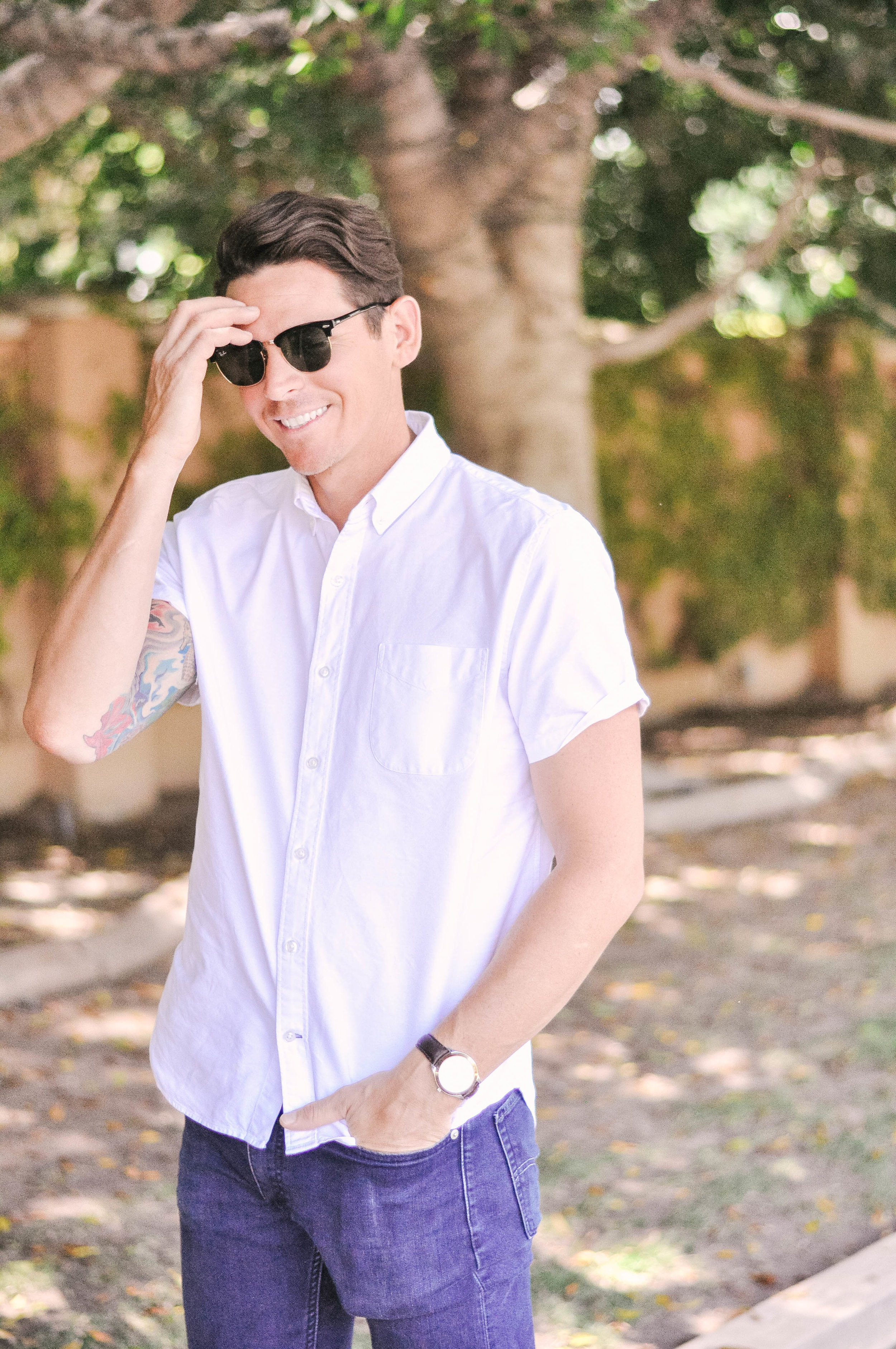 man smiling in rayban clubmaster sunglasses white button down short sleeved shirt and Levi's 511 slim jeans