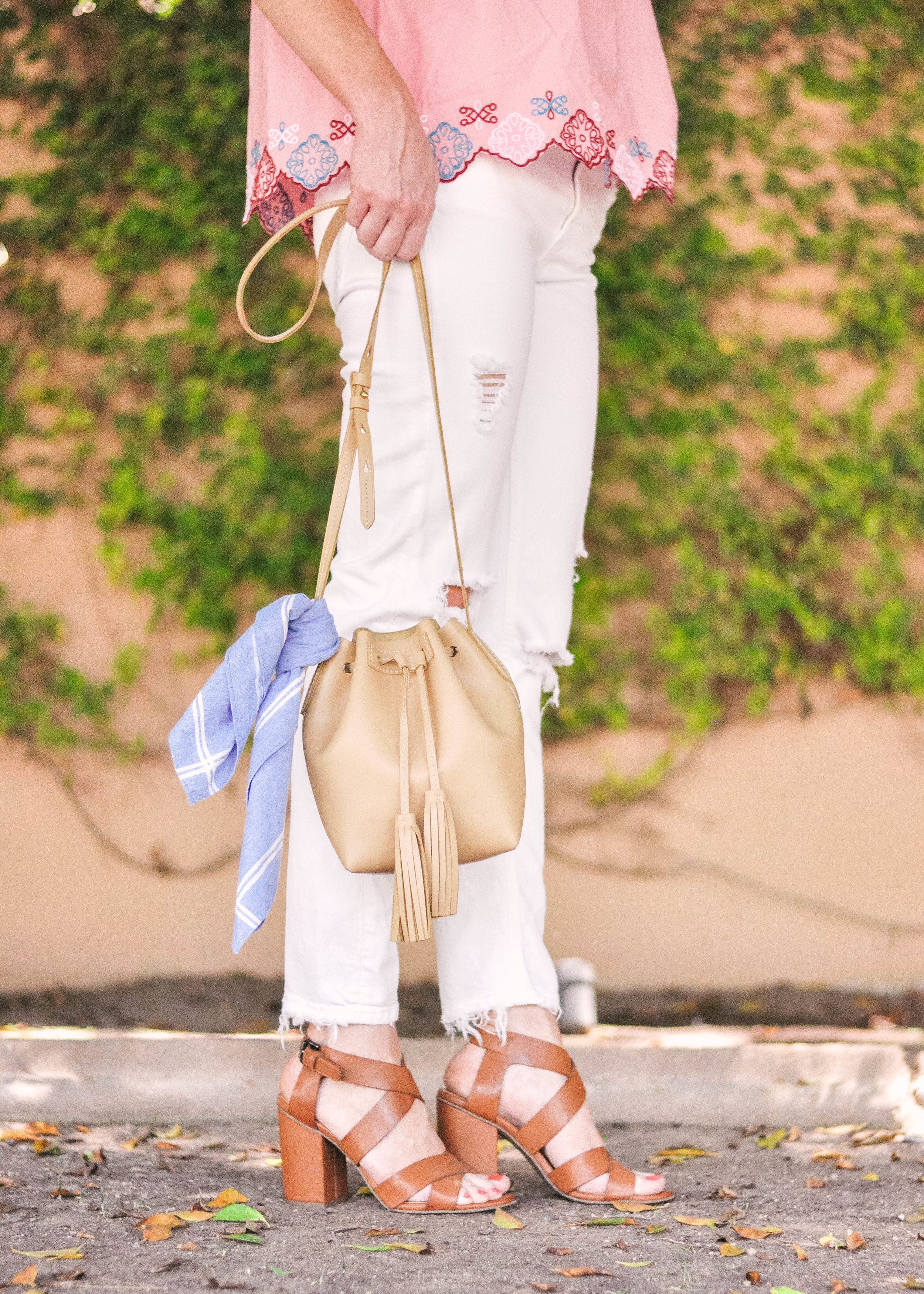 woman standing with white Zara jeans Nordstrom Sandals and tan J.Crew leather handbag
