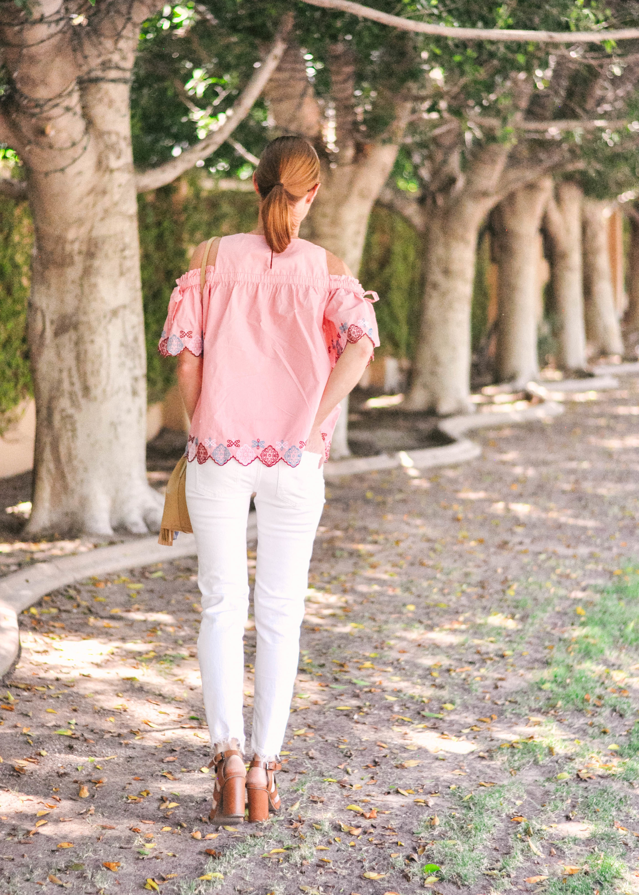 woman standing with white Zara jeans pink Loft top Nordstrom Sandals and tan J.Crew leather handbag