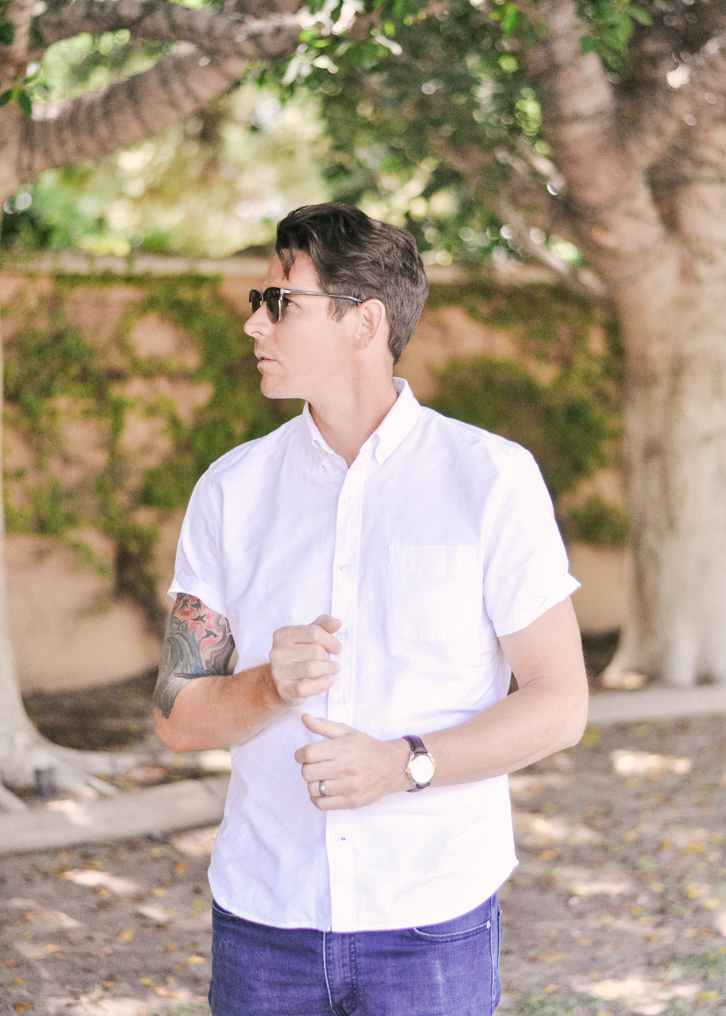 man in rayban clubmaster sunglasses white button down short sleeved shirt and Levi's 511 slim jeans
