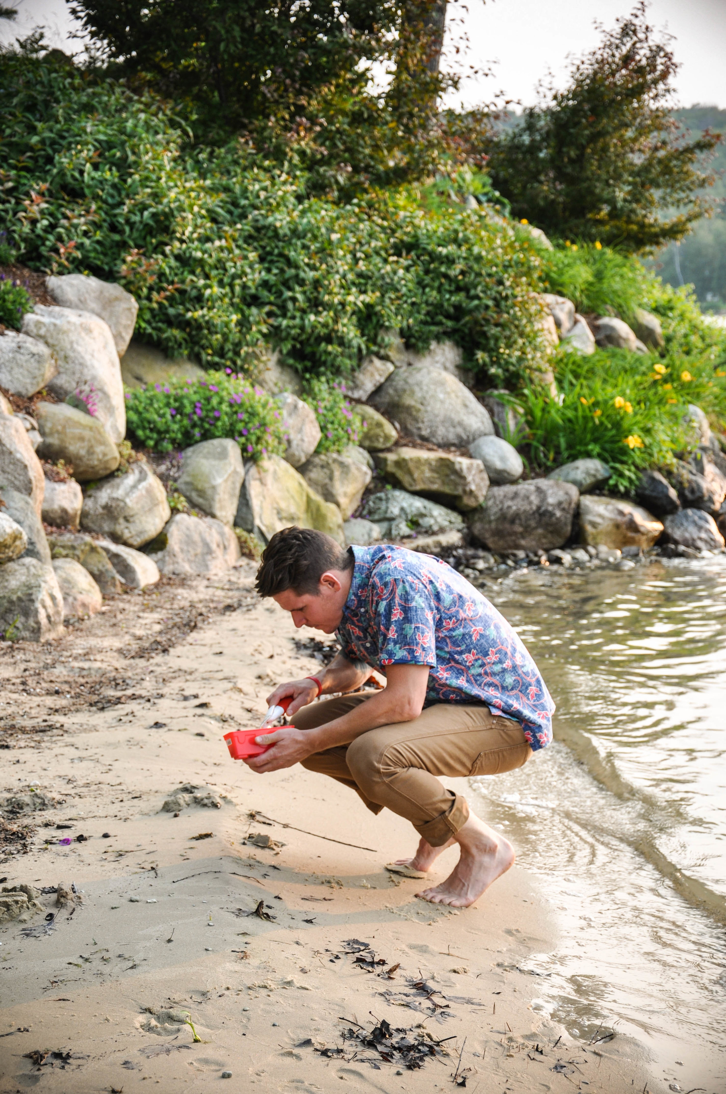 man crouched down looking at something on beach