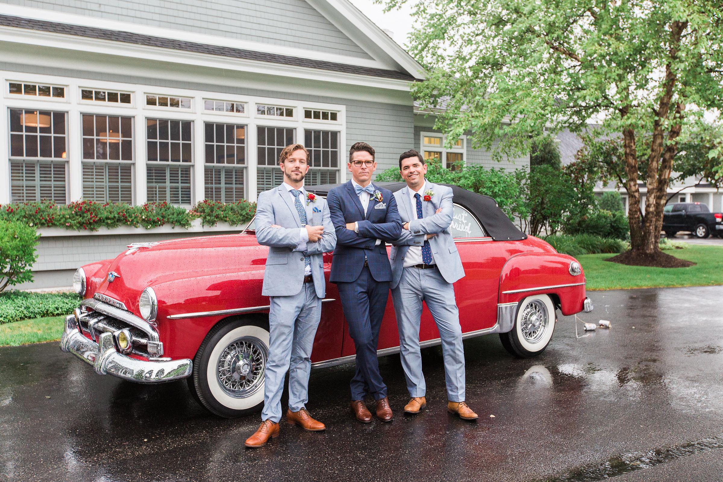 groomsmen posing in front of red car