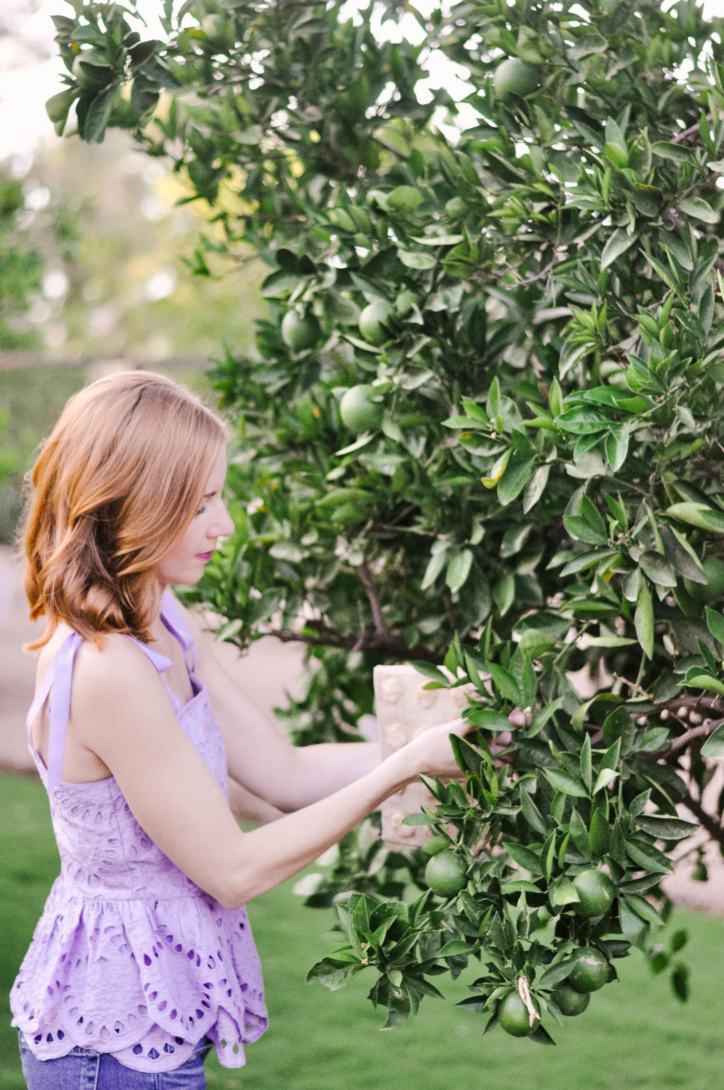 woman with red hair looking at citrus tree in J.Crew lavender eyelet tie shoulder top